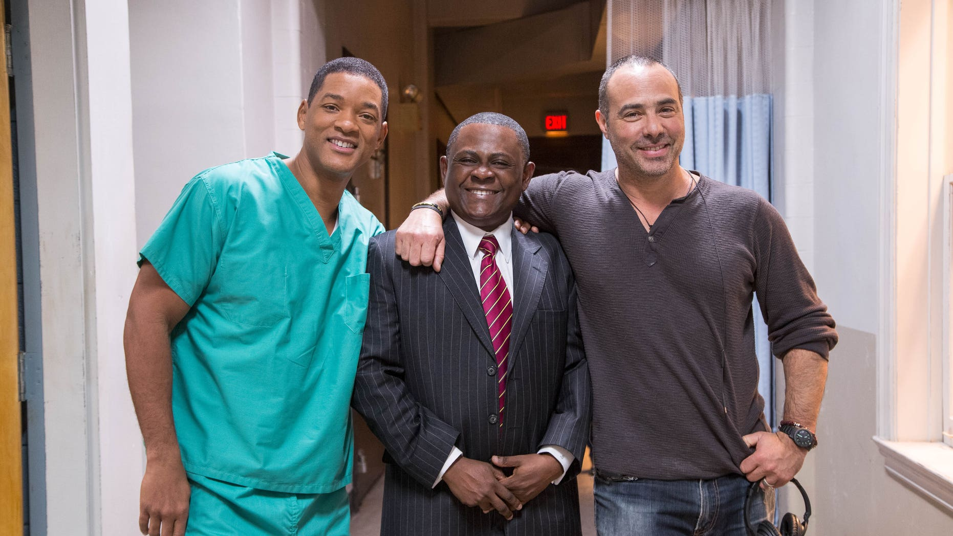 """This image released by Columbia Pictures shows, from left, Will Smith, Dr. Bennet Omalu and director Peter Landesman on the set of the film, """"Concussion."""" Smith plays Omalu, a Nigerian-born forensic pathologist in Pittsburgh who knows nothing about football when he performs the autopsy on former Steelers center Mike Webster. Omalu discovers CTE in Webster's brain, setting him on a journey that exposes the concussion crisis. (Melinda Sue Gordon/Columbia Pictures via AP)"""