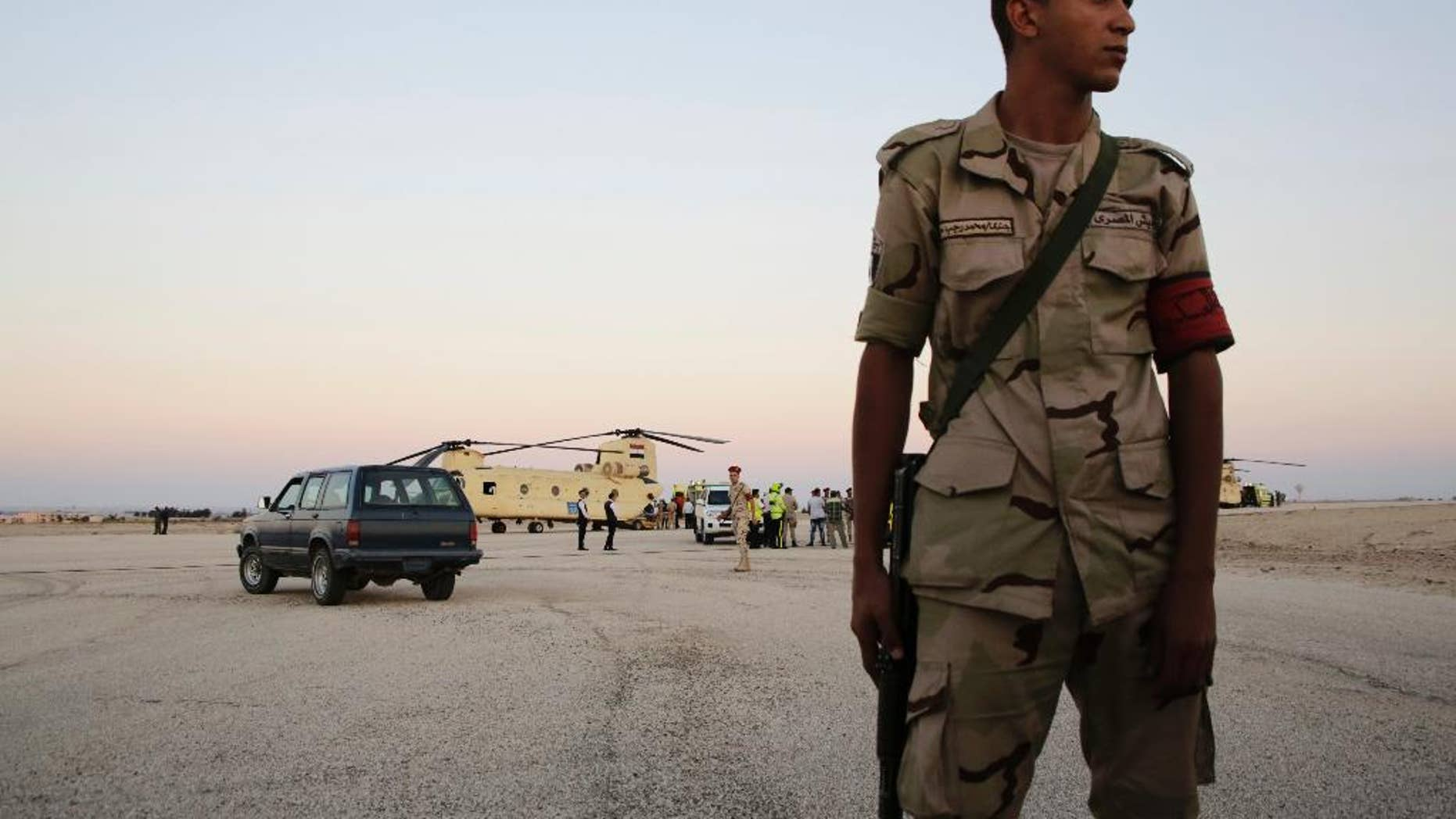 FILE - In this Saturday, Oct. 31, 2015 file photo, an Egyptian soldier stands guard as emergency workers unload bodies of victims from the crash of a Russian aircraft over the Sinai peninsula from a police helicopter to ambulances at Kabrit military airport, some 20 miles north of Suez, Egypt. Egyptians in the restive northern Sinai city of al-Arish are threatening civil disobedience to protest against what they claim to be the extrajudicial killing of six youths by security forces. (AP Photo/Amr Nabil, File)