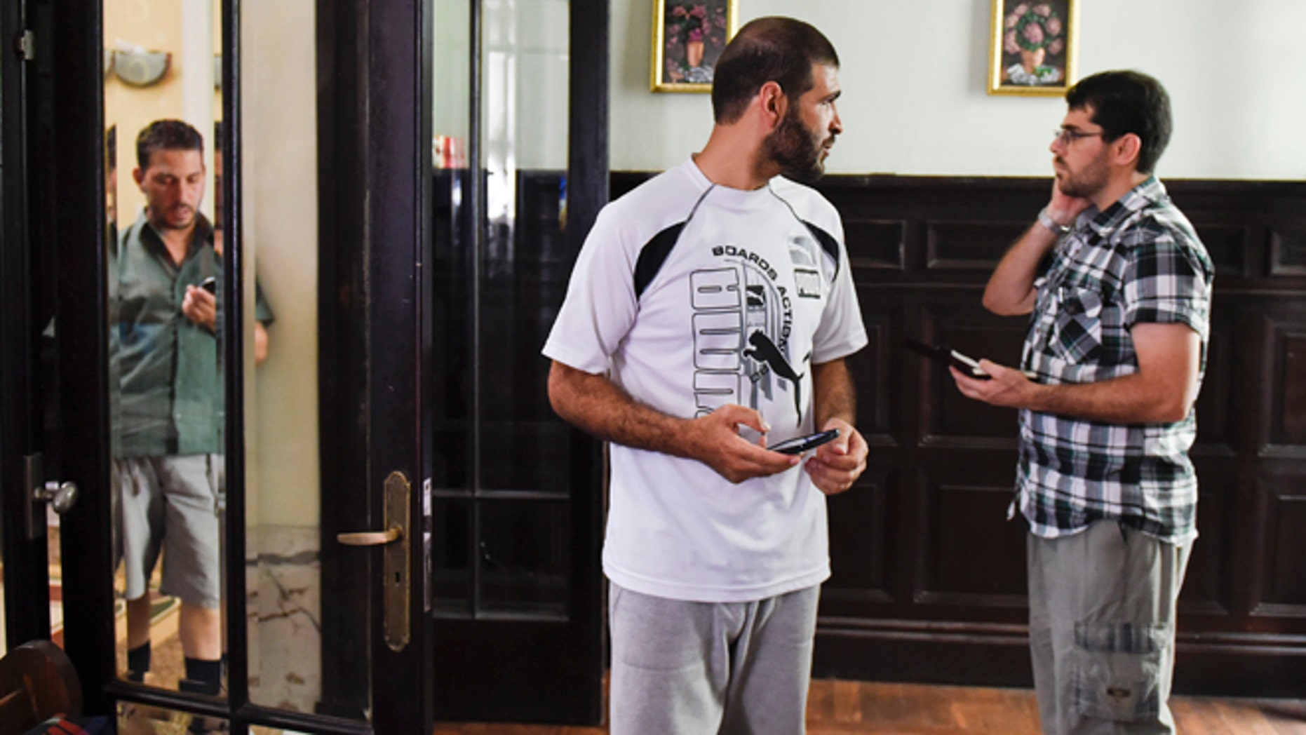 In this Feb. 24, 2015 photo, Adel bin Muhammad El Ouerghi, from Tunisia, left, Ali Husain Shaaban, from Syria, center, and Omar Abdelahdi Faraj, from Syria, right, stand inside the home they share with three other former Guantanamo detainees in Montevideo, Uruguay. Like hundreds of others at Guantanamo, the men, who were arrested in 2002, were held without charge. The U.S. released them because officials determined that they should no longer be considered a threat. (AP Photo/Matilde Campodonico)