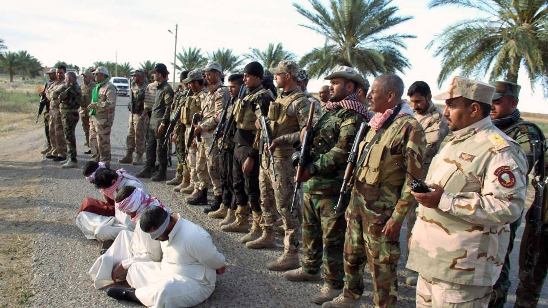 FILE - In this file photo taken Thursday, May 28, 2015, Iraq's Badr Brigades Shiite militia detain four men that they suspect of being militants of the Islamic State group outside the oil refinery in Beiji, some 155 miles (250 kilometers) north of Baghdad, Iraq. Iraqi troops backed by Shiite militias recaptured key parts of the northern refinery town of Beiji from Islamic State militants on Sunday, June 7, a general said. (AP Photo, File)