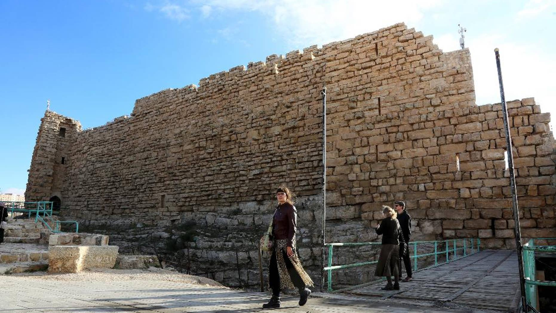 In this Wednesday, Jan. 4, 2017 photo, tourists walk near the entrance to Karak Castle, Jordan. The recent Islamic State shooting rampage at Karak Castle, a popular tourism site in Jordan, where 10 people were killed, could signal a more aggressive campaign by the extremist group to destabilize the pro-Western kingdom. A senior security official says members of the Karak cell, who were killed during the attack, had planned New Year's Eve attacks in Jordan, using five explosives belts. Jordan's government tries to allay concerns, saying its security forces can contain any threat. (AP Photo/Raad Adayleh).