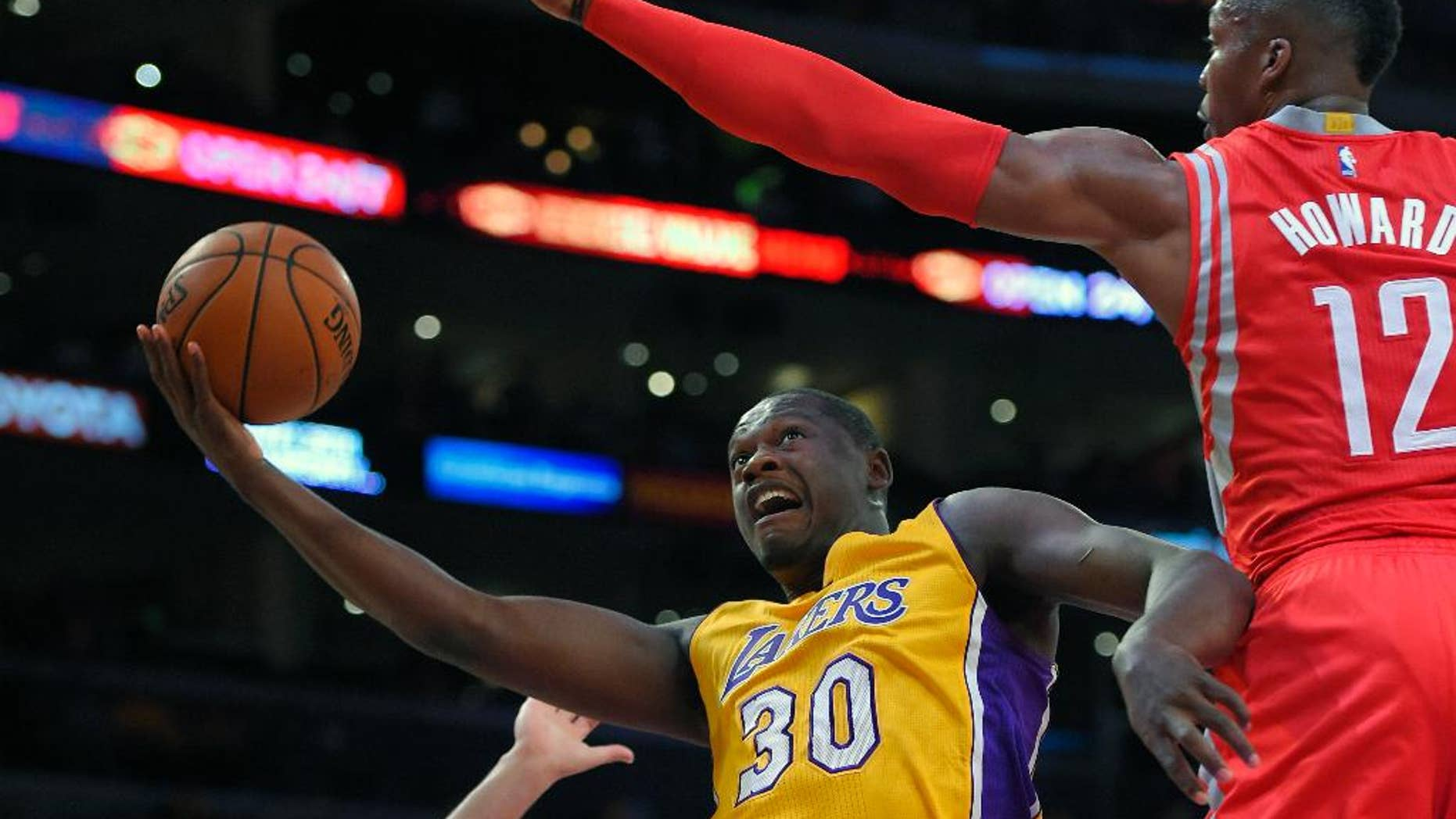 Los Angeles Lakers forward Julius Randle, left, puts up a shot as Houston Rockets center Dwight Howard defends during the first half of an NBA basketball game, Tuesday, Oct. 28, 2014, in Los Angeles. (AP Photo/Mark J. Terrill)