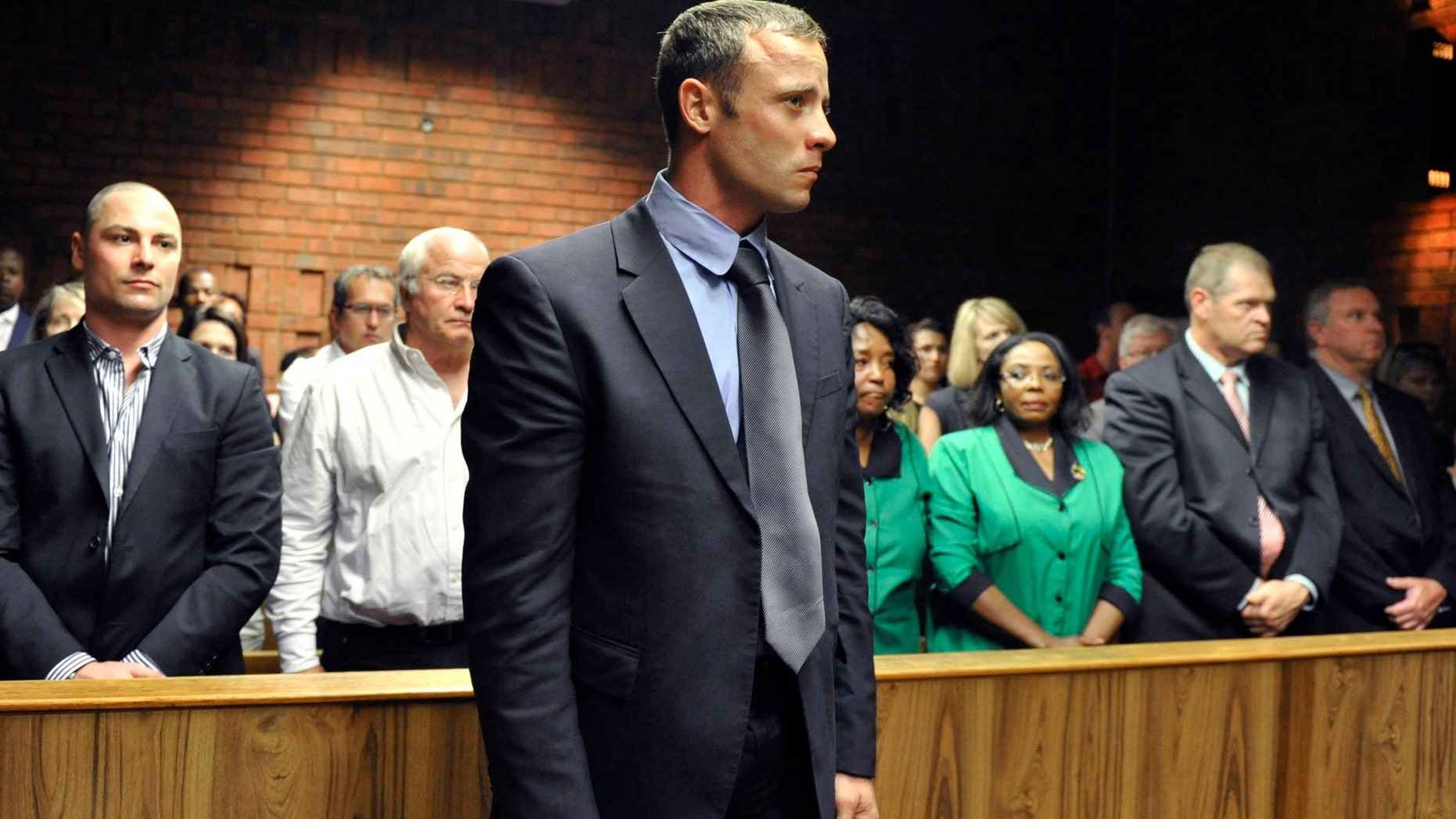 Olympian Oscar Pistorius stands following his bail hearing in Pretoria, South Africa, Tuesday, Feb. 19, 2013. Pistorius fired into the door of a small bathroom where his girlfriend was cowering after a shouting match on Valentine's Day, hitting her three times, a South African prosecutor said Tuesday as he charged the sports icon with premeditated murder. The magistrate ruled that Pistorius faces the harshest bail requirements available in South African law. He did not elaborate before a break was called in the session. (AP Photo)