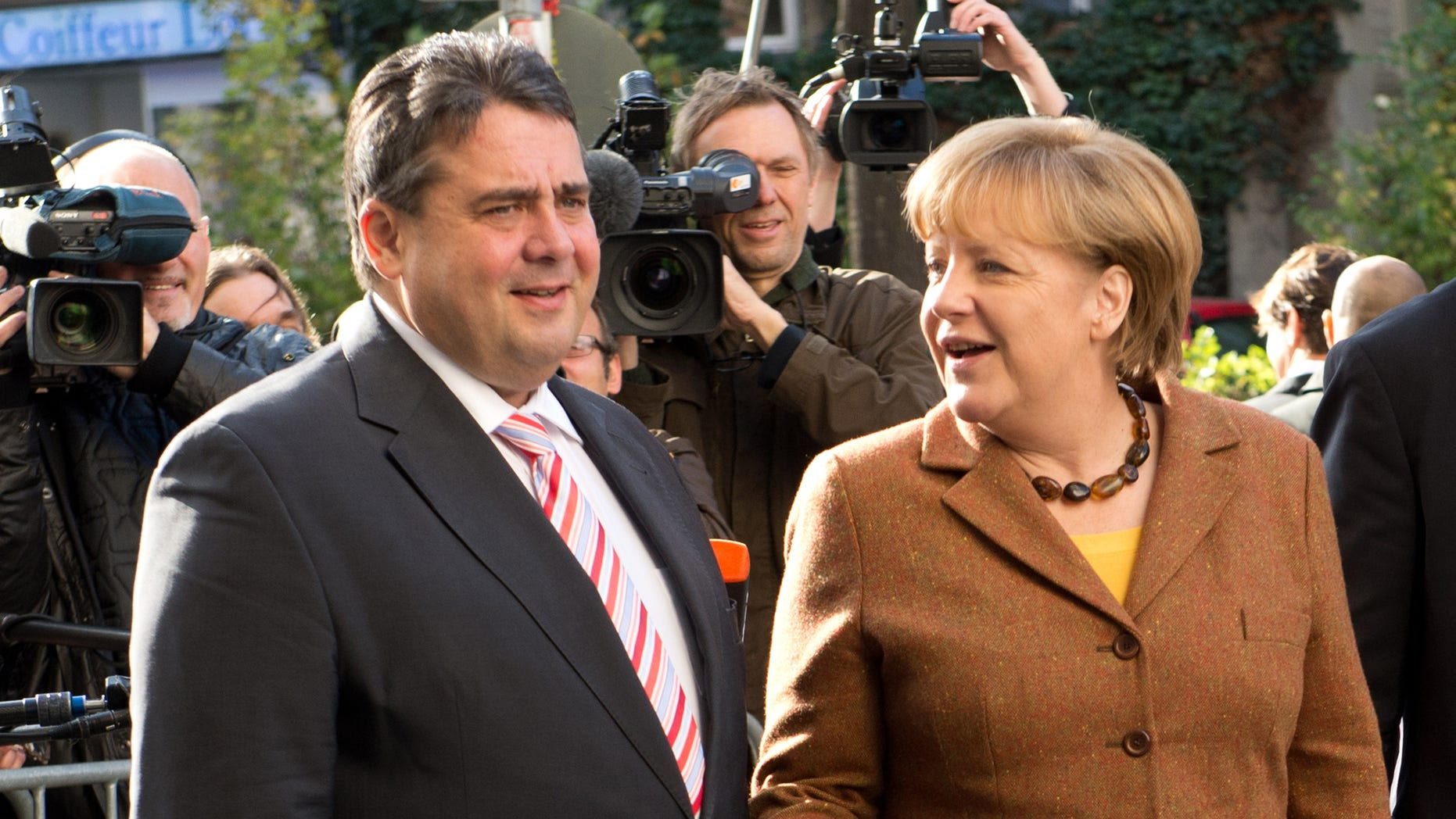 Social Democratic Party, SPD, chairman Sigmar Gabriel, left, welcomes Angela Merkel, right, German Chancellor and chairwoman of the Christian Democratic Union, CDU, center, at the Social Democrat's headquarters for coalition talks in Berlin, Wednesday, Oct. 30, 2013. Following the Sept. 22 national elections Chancellor Merkel and her Christian parties' bloc are negotiating the second week on forming a coalition with the Social Democratic Party. (AP Photo/dpa, Rainer Jensen)