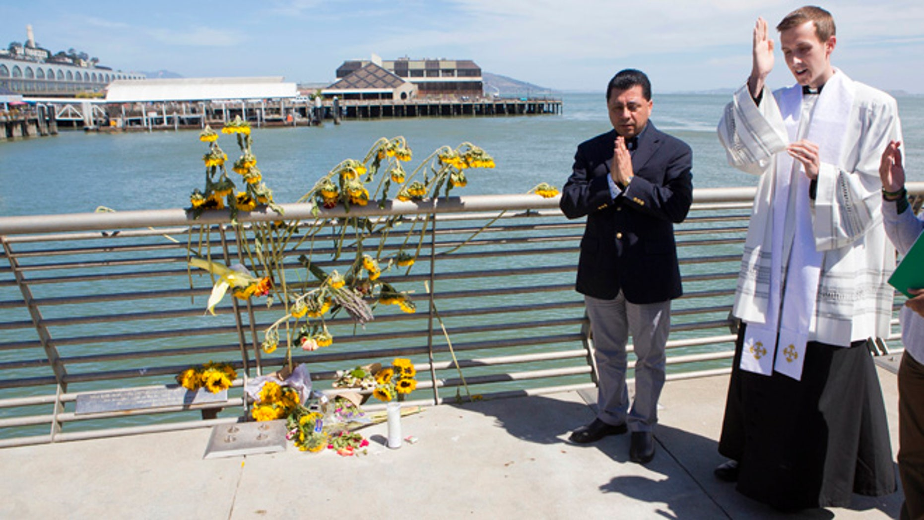 Father Cameron Faller and Julio Escobar conduct a vigil for Kathryn Steinle on Pier 14 in San Francisco, July 6, 2015.