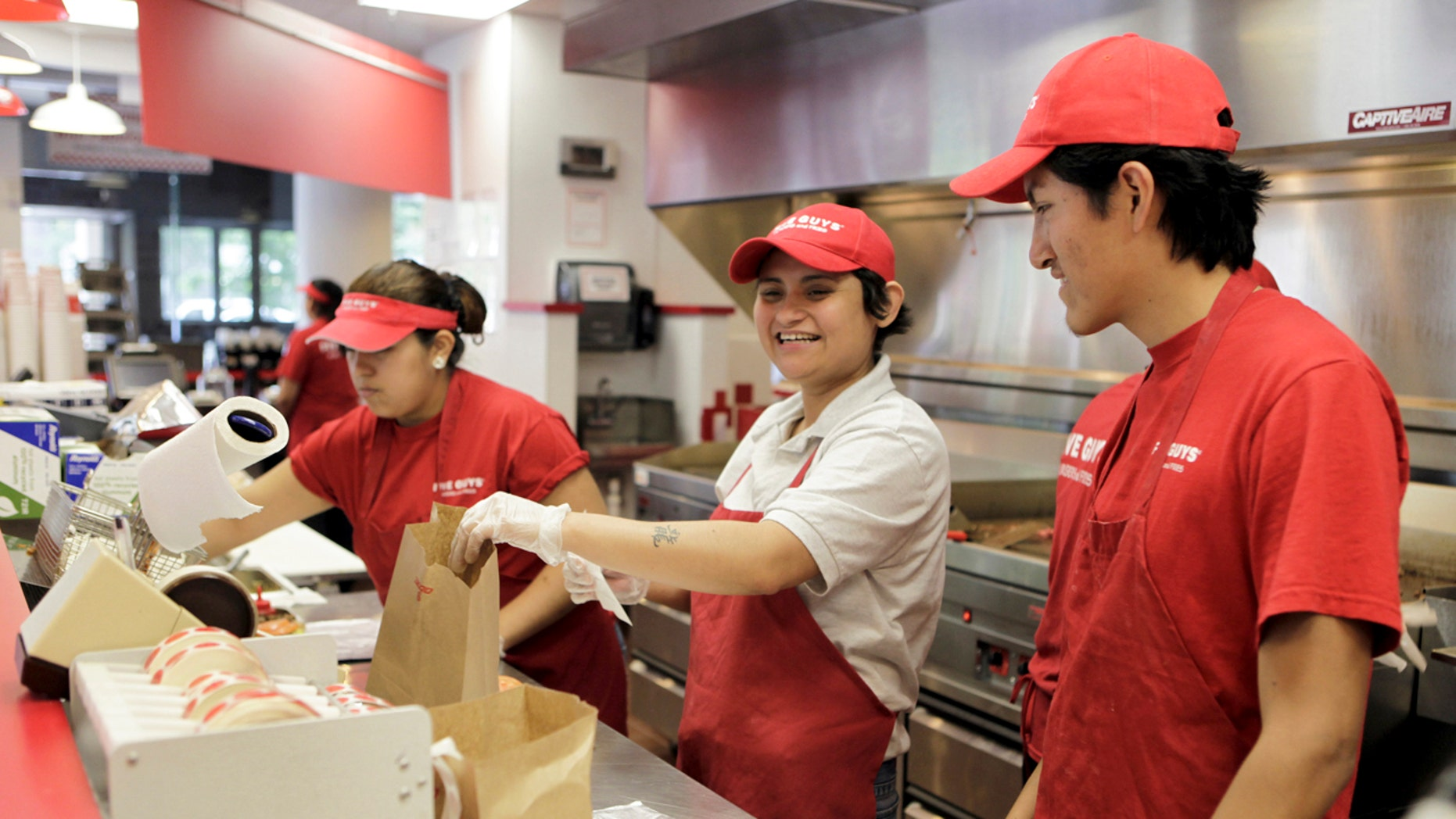 Manager Kely Guardado (C) prepares hamburgers at a Five Guys restaurant in Washington, May 26, 2010. The weak U.S. economy is no match for fast-growing Five Guys Burgers and Fries, where the standard hamburger has two patties and french fries are served in a cup with an extra scoop on the side for good measure. Picture taken May 26, 2010. To match Analysis RESTAURANTS/   REUTERS/Yuri Gripas (UNITED STATES - Tags: FOOD BUSINESS) - RTR2EFDK