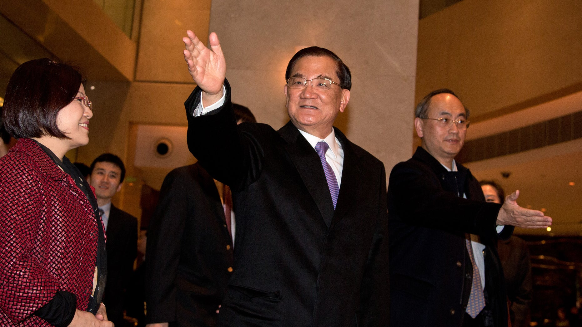 Taiwan's former vice president Lien Chan, center, waves to journalists upon arrival at a hotel in Beijing Sunday, Feb. 24, 2013. Lien Chan leads a business and politician delegation  to Beijing for a three day visit and will meet with Chinese President Hu Jintao and Communist Party Secretary General and the country's new leader Xi Jinping. (AP Photo/Andy Wong)