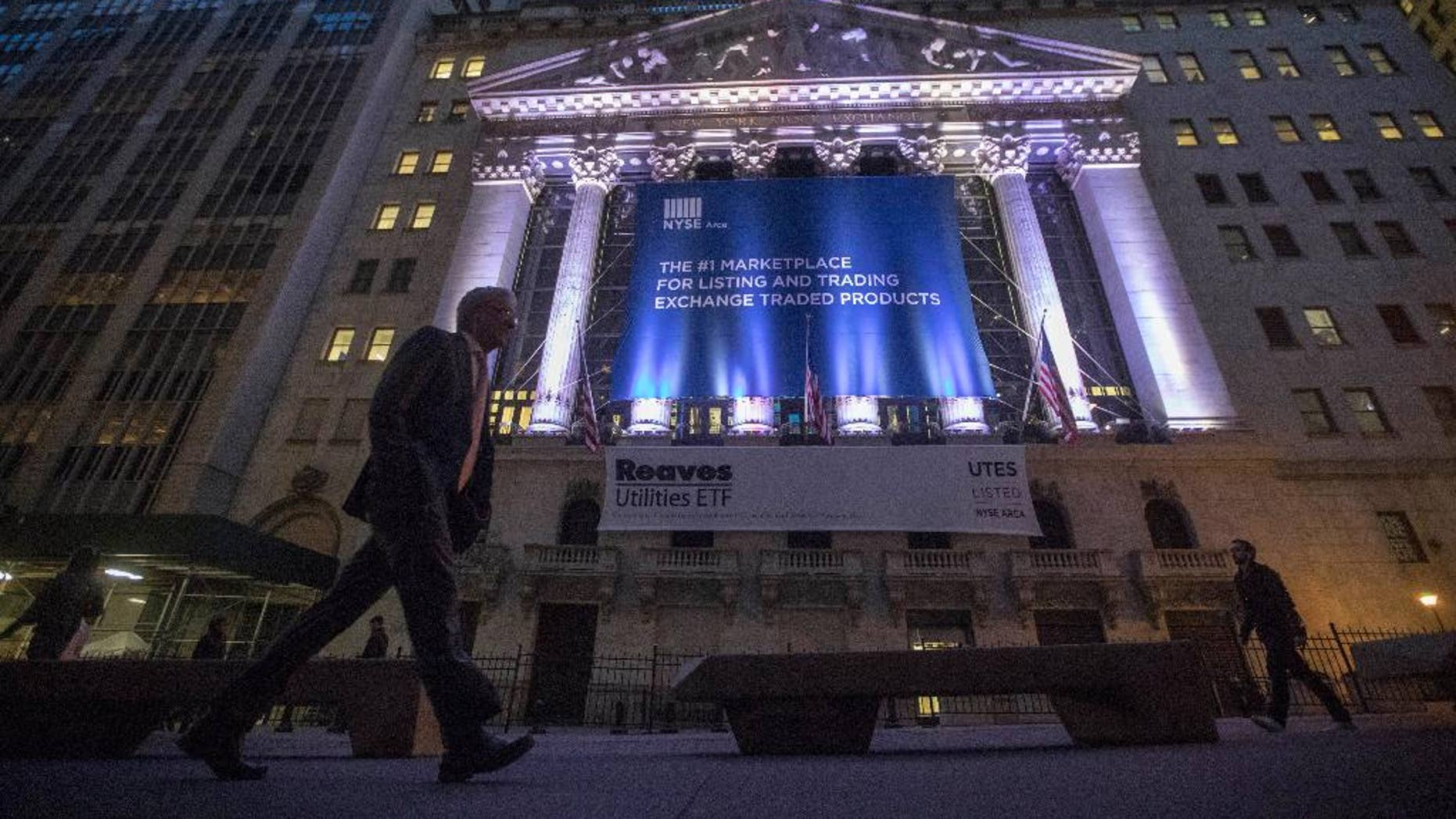 FILE - In this Oct. 25, 2016, photo, a pedestrian passes the New York Stock Exchange, in lower Manhattan. U.S. stocks edged higher Friday morning, Dec. 30, 2016, on the final day of trading for the year. High-dividend stocks like phone companies and utilities fell the most, giving back some of the gains from a day earlier. Real estate stocks led the gainers. Trading was quiet ahead of the New Year's Day holiday. (AP Photo/Mary Altaffer, File)