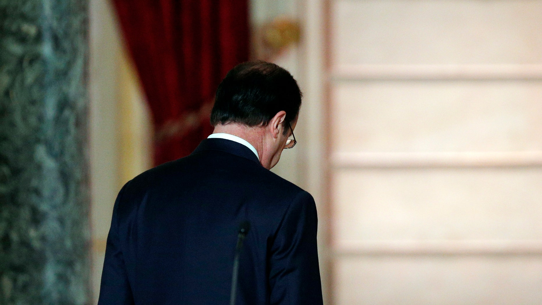 French President Francois Hollande leaves after his annual news conference, Tuesday, Jan.14, 2014 at the Elysee Palace in Paris. Hollande is promising to cut 50 billion euros in public spending over 2015-2017 to try to improve the indebted economy. Hollande, a Socialist, came to office in 2012 on pledges to avoid the painful austerity measures carried out by neighboring Spain and Italy. But France's economy has suffered two recessions in recent years and growth is forecast at an anemic 0.2 percent in 2013. (AP Photo/Christophe Ena)