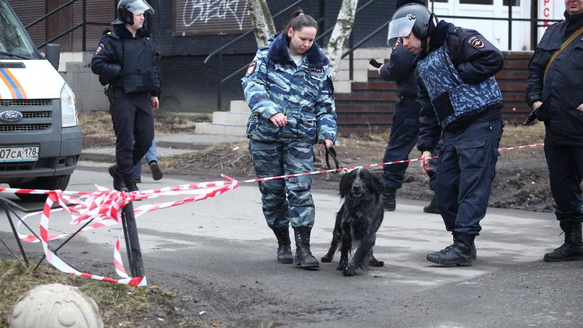 A Russian police officer with a sniffing dog crossing a police line in St. Petersburg Thursday.