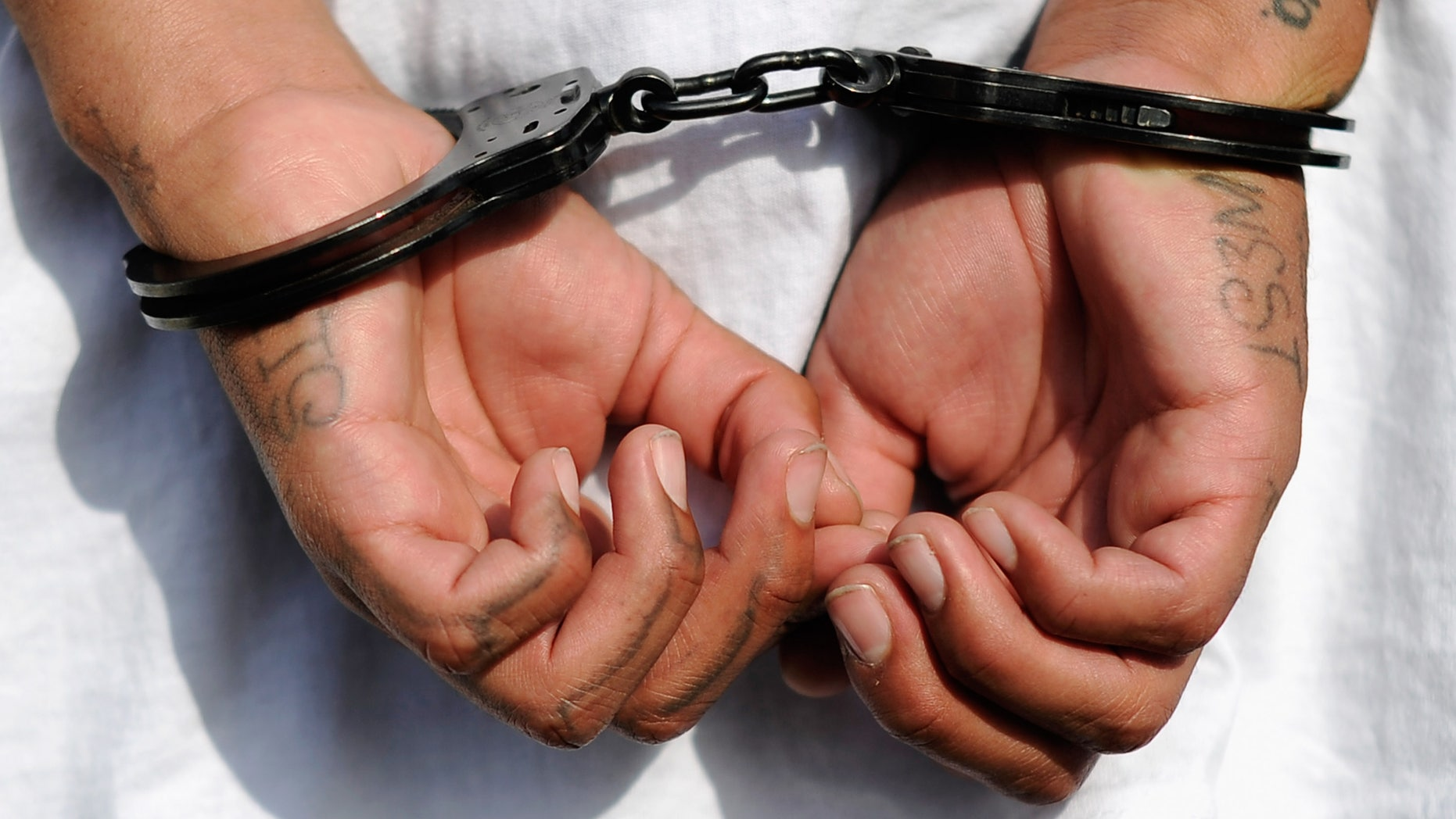 "LOS ANGELES, CA - APRIL 29:  Handcuffs are seen on the hands of a twenty-year old ""Street Villains"" gang member who was arrested by Los Angeles Police Department officers from the 77th Street division on April 29, 2012 in Los Angeles, California. The 77th Street division patrol the same neighborhood that truck driver Reginald Denny was nearly beaten to death by a group of black assailants at the intersection of Florence and Normandie Avenues. It?s been 20 years since the verdict was handed down in the Rodney King case that sparked infamous Los Angeles riots.  (Photo by Kevork Djansezian/Getty Images)"