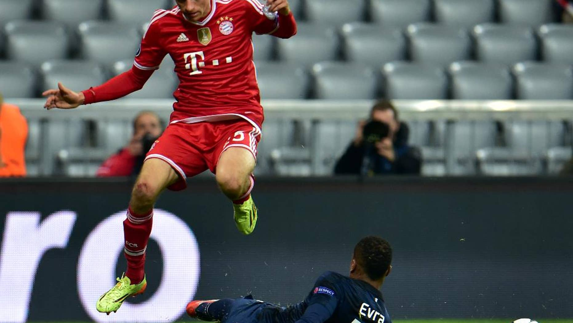 Bayern's Thomas Mueller, left, and Manchester United's Patrice Evra, right, challenge for the ball during the Champions League quarterfinal second leg soccer match between Bayern Munich and Manchester United in the Allianz Arena in Munich, Germany, Wednesday, April 9, 2014. (AP Photo/Kerstin Joensson)