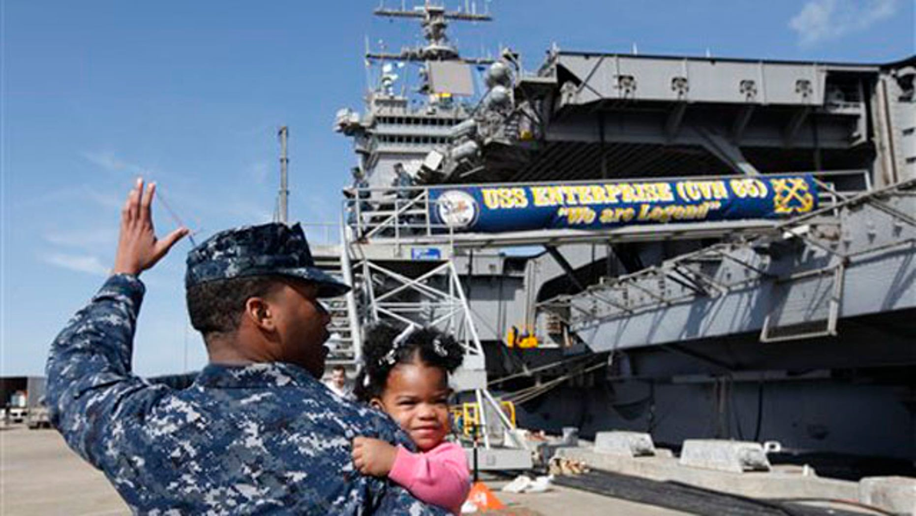 March 8, 2012: In this photo, Petty Officer 3rd Class Michael Joseph, carries his daughter Maleah, 1, to his re-enlistment ceremony aboard the nuclear powered aircraft carrier USS Enterprise at the Norfolk Naval Station in Norfolk, Va.