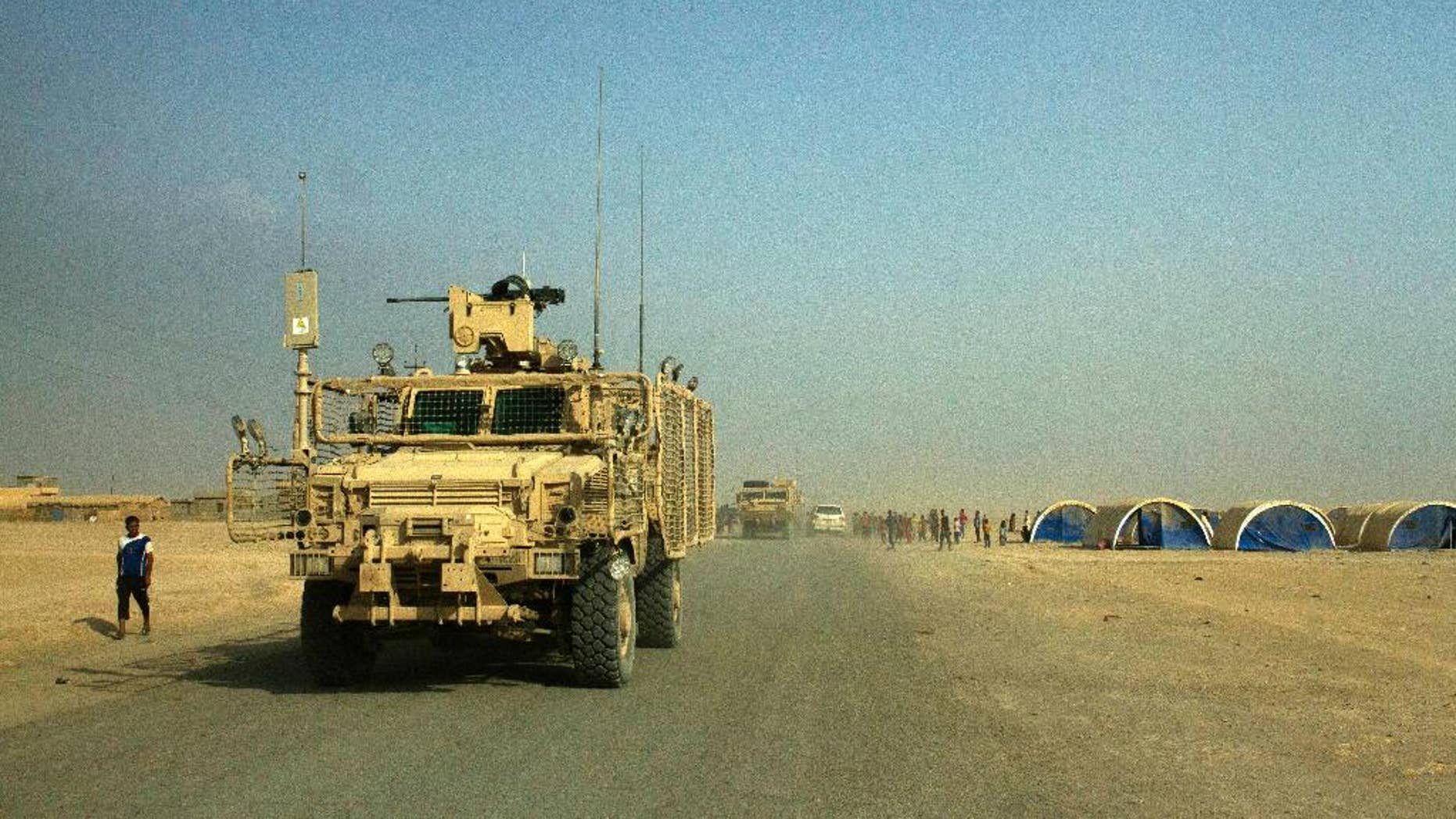 Armored coalition vehicles outside the Qayara air base in August.