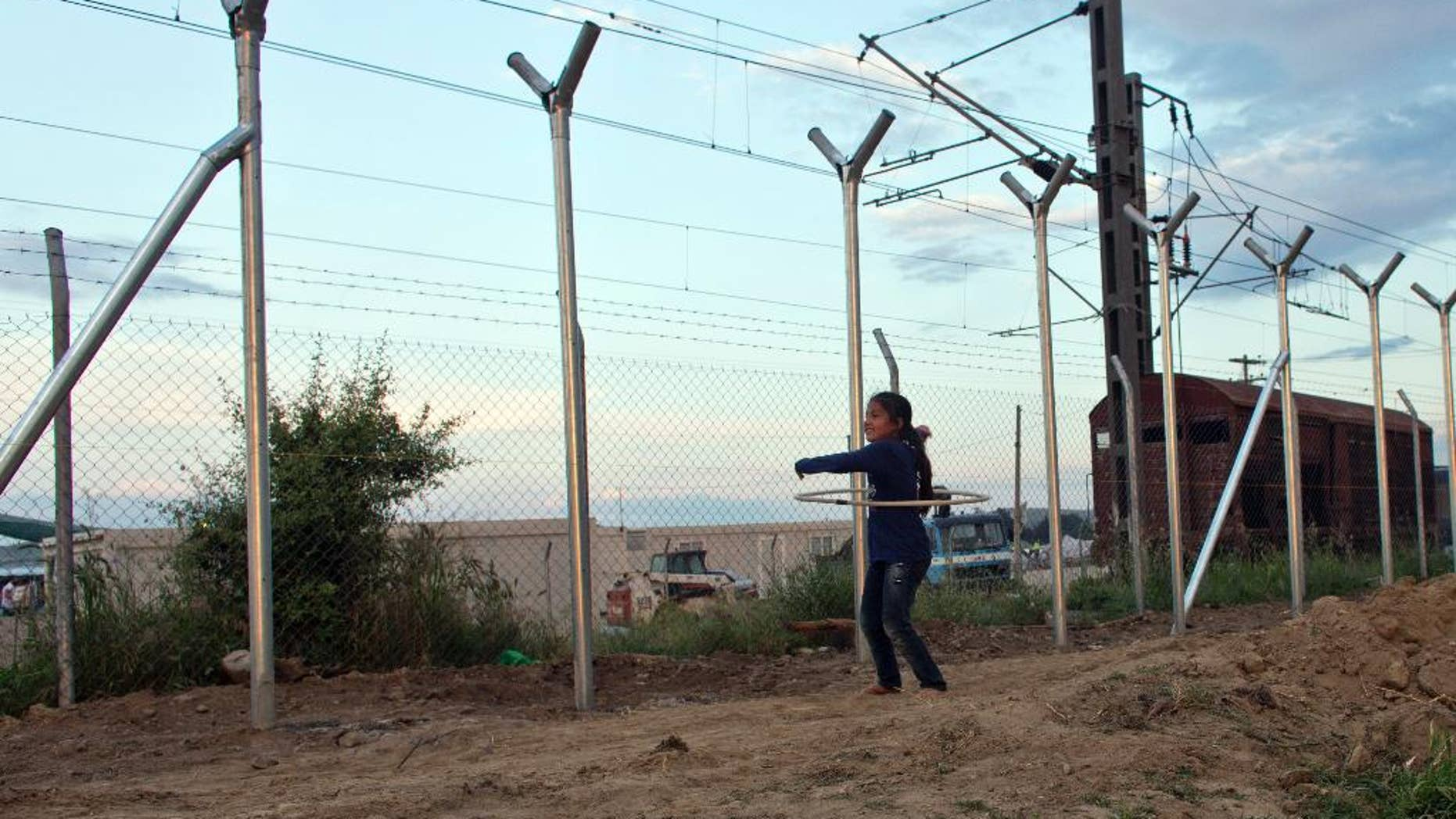A girl plays next to the fence on the Macedonian border in Idomeni, Greece, Thursday, May 19, 2016.  Thousands of stranded refugees and migrants have camped in Idomeni for months after the border was closed. (AP Photo/Darko Bandic)