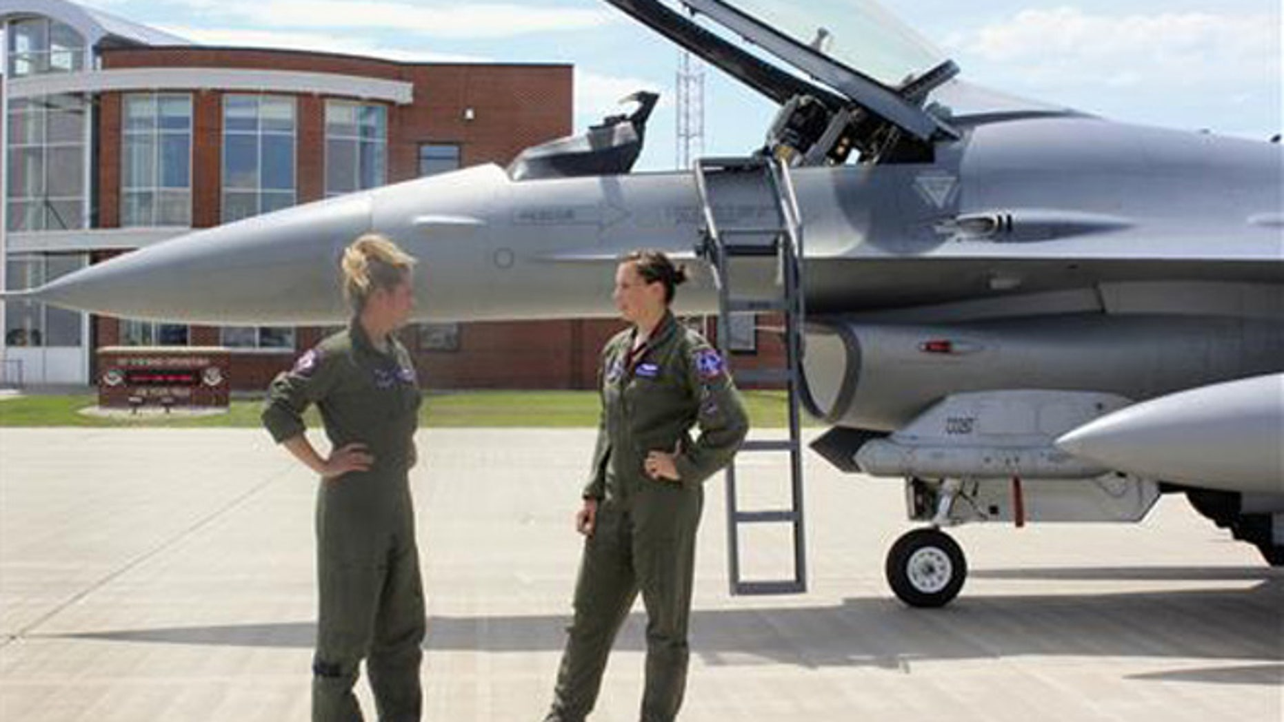 In this Tuesday, July 19, 2016, photo, Capt. Valerie Vanderostyne, left, and Capt. Shanon Davis, both with the South Dakota Air National Guard, chat alongside an F-16 Fighting Falcon at Joe Foss Field in Sioux Falls, S.D.