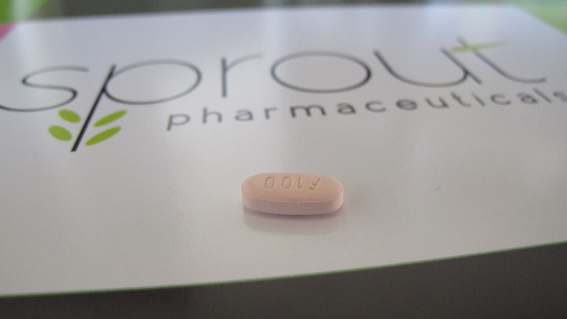 A tablet of flibanserin sits on a brochure for Sprout Pharmaceuticals in the company's Raleigh, N.C., headquarters. (AP Photo/Allen G. Breed)