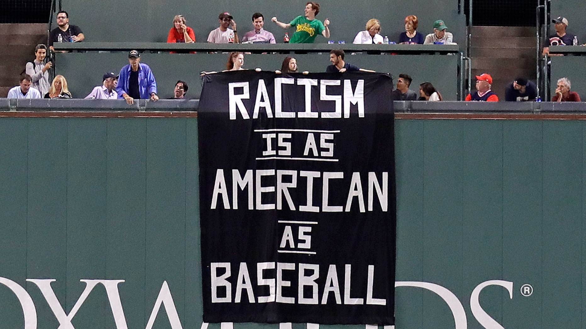 A banner is unfurled over the left field wall at Fenway Park in Boston Wednesday night.
