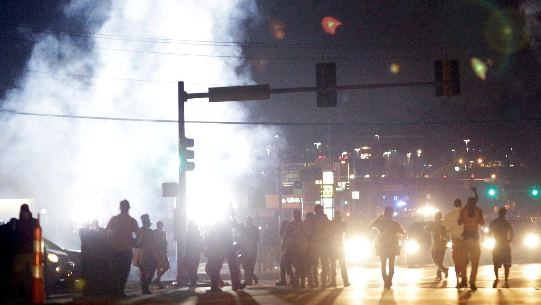 Aug. 18, 2014: People stand near a cloud of tear gas in Ferguson, Mo. during protests for the Aug. 9 shooting of unarmed black 18-year-old Michael Brown by a white police officer