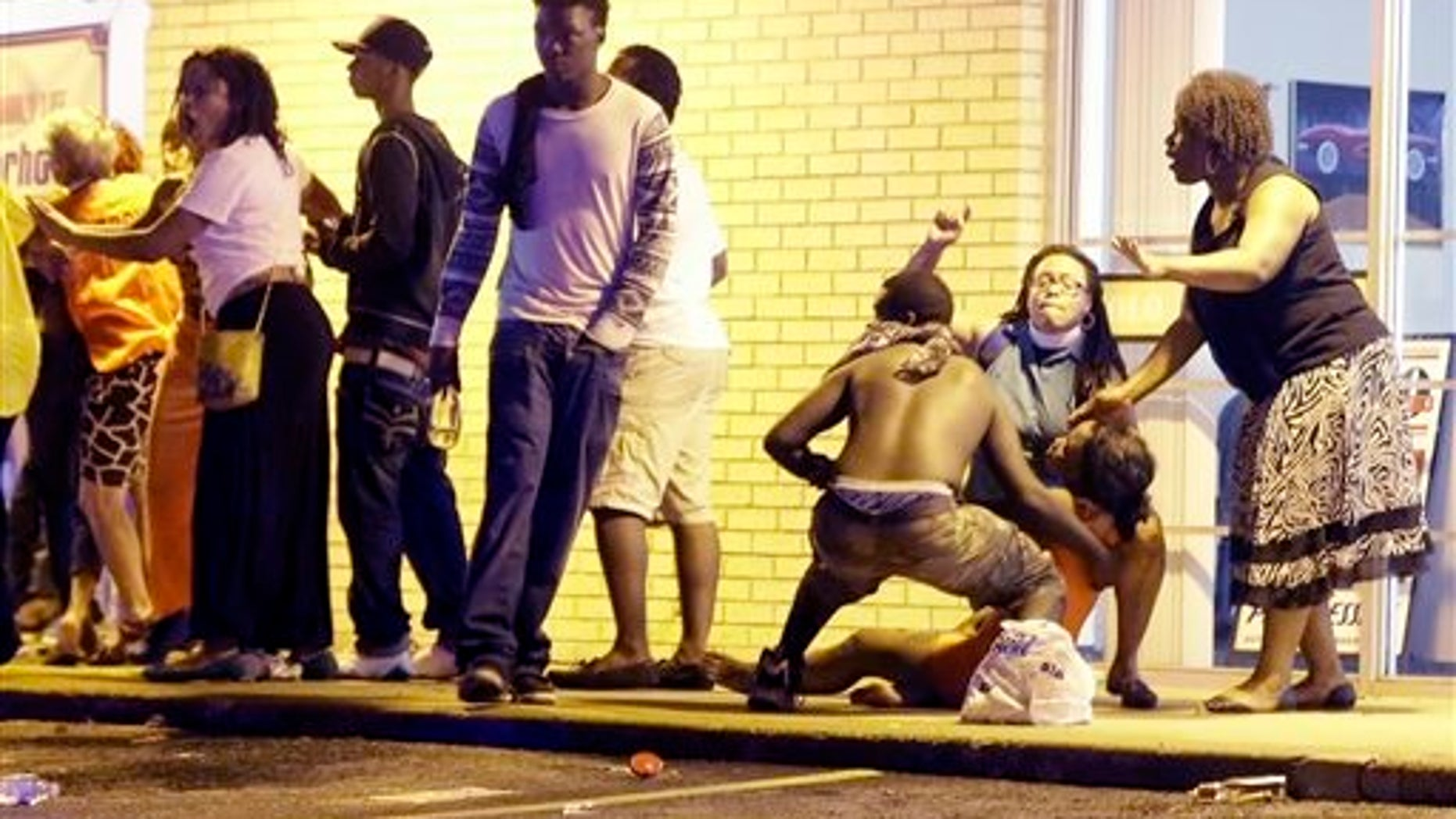 People come to the aid of a distraught woman after gunshots were fired near a protest in Ferguson, Mo., Sunday, Aug. 9, 2015. The one-year anniversary of Michael Brown's death in Ferguson began with a march in his honor and ended with a protest that was interrupted by gunfire. (AP Photo/Jeff Roberson)
