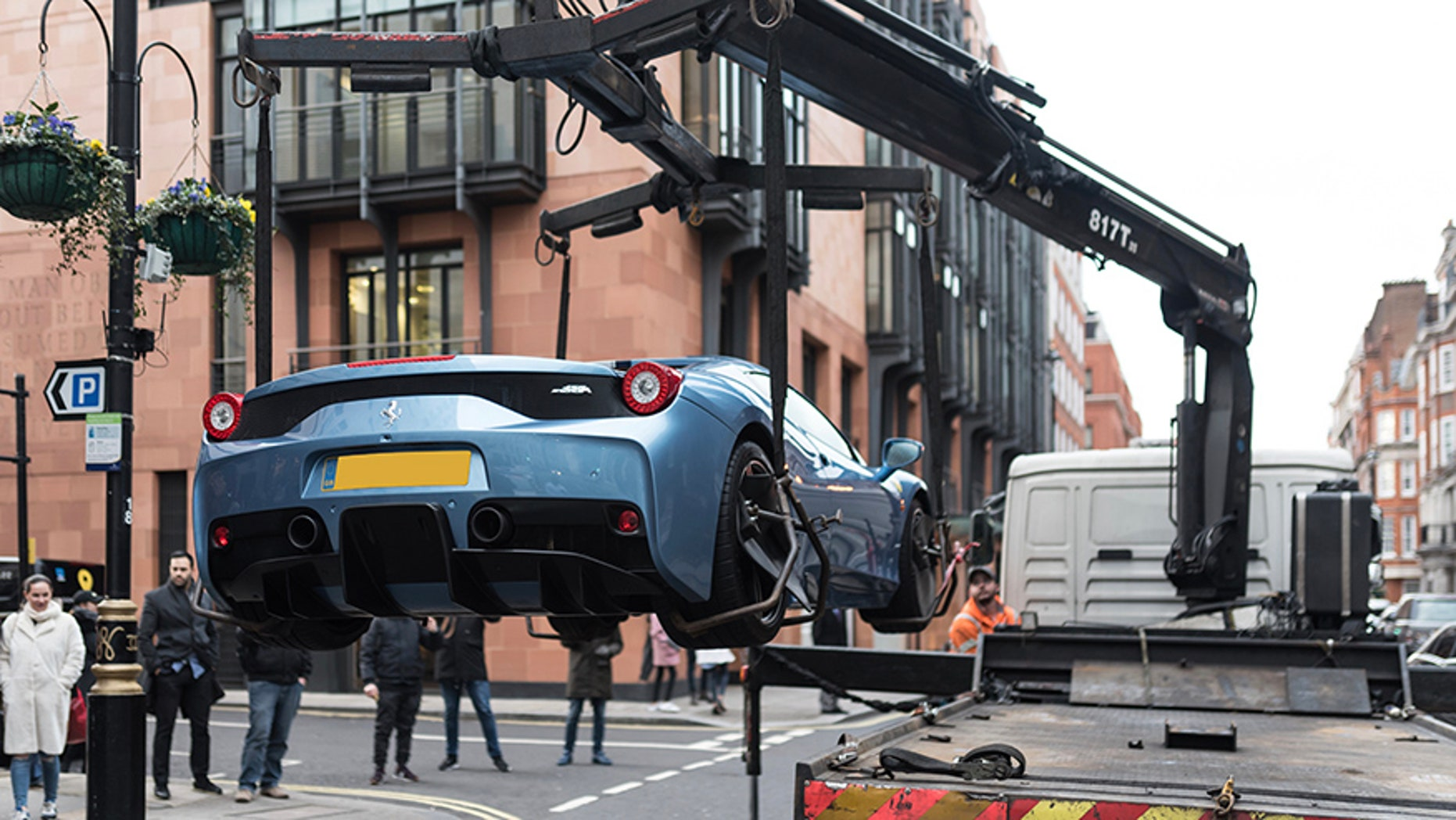 """This is the moment cops in London seized a limited edition Ferrari worth half a million pounds - because its young owner didn't have car insurance. See SWNS story SWFERRARI; Stunned onlookers in posh Mayfair watched the bizarre scene unfold on Sunday afternoon as the Ferrari 458 Speciale Aperta, one of only 499 ever made, was lifted onto a towing truck. Cops said the driver was reported on suspicion of using the expensive car, which is even more sought-after because it is one of the few with a right-hand drive, without insurance. An eyewitness said:""""The young man was in a baby blue Ferrari worth probably around £600,000.""""He was driving in convoy through Mayfair with his dad who was in a Porsche 918."""""""