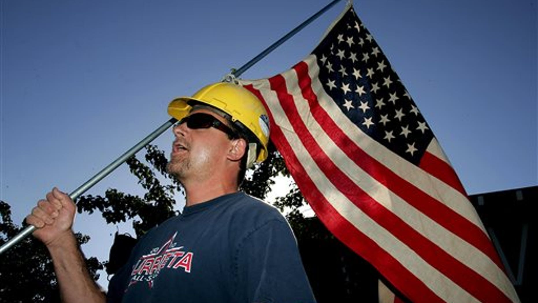 Paul Hathaway, of Murrieta, Calif., holds a U.S. flag as he shouts outside Murrieta Mesa High School in Murrieta, Calif., where city, Riverside County and federal officials spoke about a  plan to process immigrants detained in Texas at the Murrieta U.S. Border Patrol facility, Wednesday, July 2, 2014. (AP Photo/The Press-Enterprise, Terry Pierson)