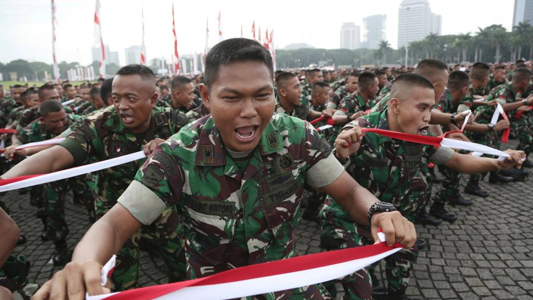 Indonesian soldiers perform national flag -colored headbands during a military-sponsored interfaith rally held ahead of the planned Dec. 2 Muslim protest against Jakarta Governor Basuki Tjahaja Purnama in Jakarta, Indonesia, Wednesday, Nov. 30, 2016. Thousands of Indonesians have joined interfaith rallies around the country organized by the military in an attempt todemonstrate national unity as religious and racial tensions divide the world's largest Muslim nation. (AP Photo/Achmad Ibrahim)