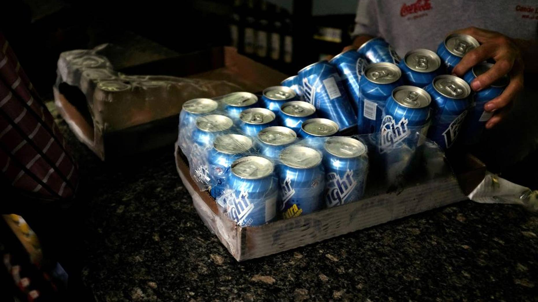 FILE - In this July 31, 2015 file photo, a liquor store worker unpacks a case of Polar beer, in downtown Caracas, Venezuela. Cerveceria Polar announced Friday, April 29, 2016,  it has shut down beer production at its factory in Carabobo, the last of its four, due to a shortage of imported supplies. (AP Photo/Fernando Llano, File)