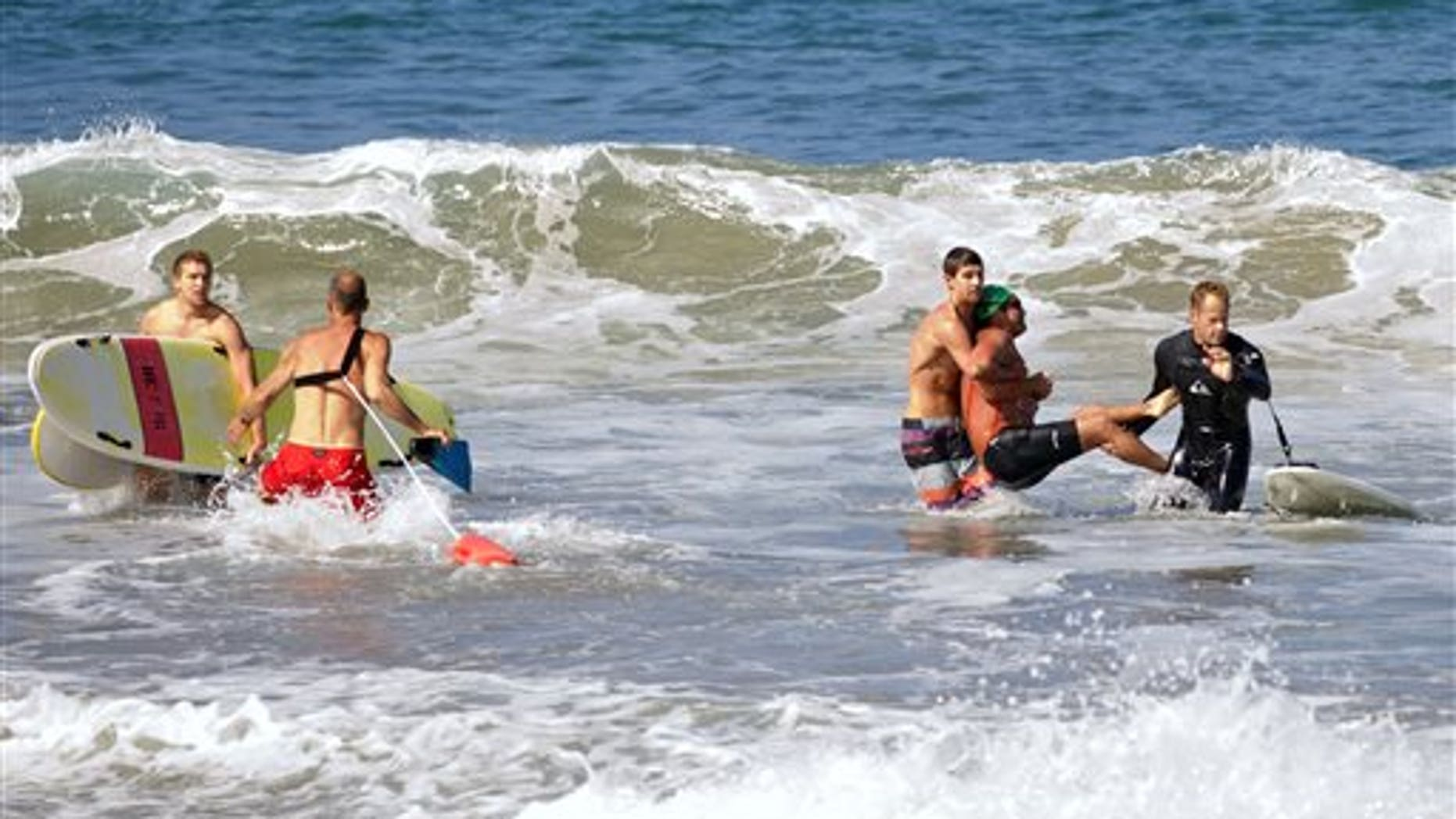 In this photo by Laura Joyce of goofyfootphotography.com, two men carry a swimmer, second from right, after he was bitten by a great white shark, as lifeguards close in at left in the ocean off Southern Californias Manhattan Beach, Saturday, July 5, 2014. The man, who was with a group of long-distance swimmers when he swam into a fishing line, was bitten on a side of his rib cage according to Rick Flores, a Los Angeles County Fire Department spokesman. The mans injuries were not life-threatening and he was taken to a hospital conscious and breathing on his own, Flores said. (AP Photo/goofyfootphotography.com, Laura Joyce)