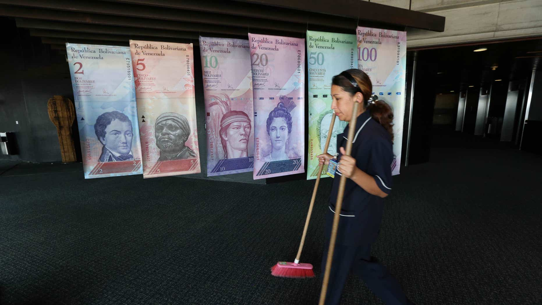A cleaning woman walks by replicas of Venezuela's currency bills, hung in a hallway at the Central bank office building in Caracas, Venezuela, Tuesday, Feb. 10, 2015. Venezuela's  Minister of Economy, Finance and Public Banking, Rodolfo Marco Torres and Venezuela's Central Bank Chairman Nelson J. Merentes announced a new system they will allow a free-floating exchange rate for the country's battered currency while maintaining a subsidized rate for key imports. Venezuela has maintained strict currency controls since 2003. (AP Photo/Ariana Cubillos)