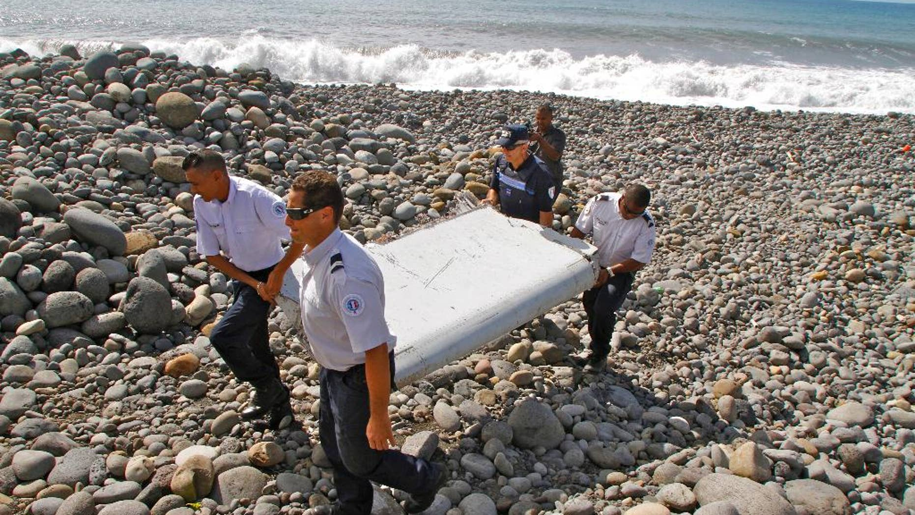 FILE - In this July 29, 2015, file photo, French police officers carry a piece of debris from a plane known as a flaperon in Saint-Andre, Reunion Island. The barnacle-encrusted part was the first trace of Malaysia Airlines Flight 370 that disappeared two years ago. Malaysia's confirmation on Thursday, May 12, 2016, that other debris found in March 2016 came from missing Malaysia Airlines Flight 370 brings to five the number of parts that have been recovered from the aircraft that vanished two years ago. (AP Photo/Lucas Marie, File)