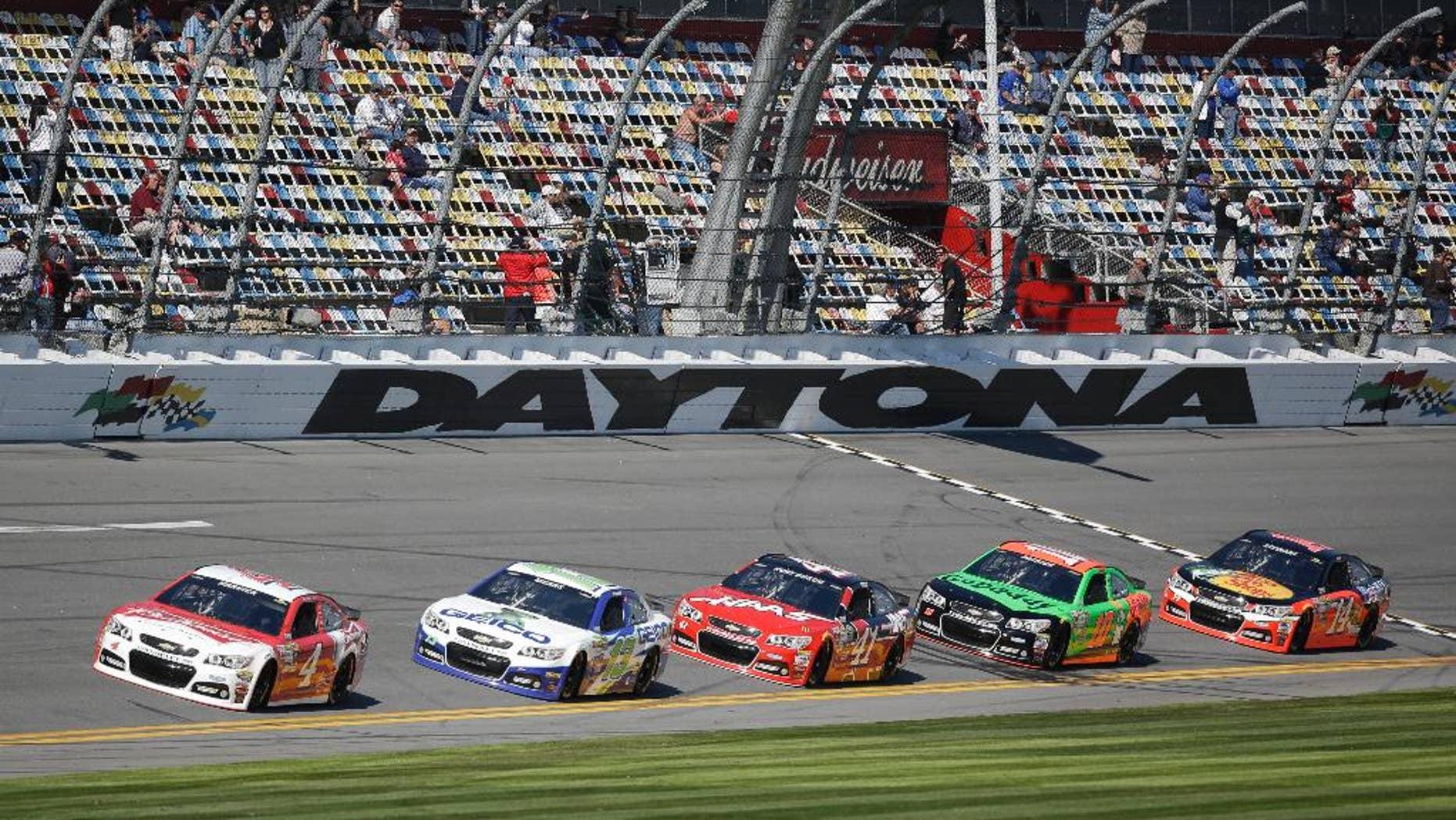 Cars qualifying for the Daytona 500 NASCAR Sprint Cup Series auto race, from left to right, Kevin Harvick (4), Casey Mears (13), Kurt Busch (41), Danica Patrick (10) and Tony Stewart (14) runs laps at Daytona International Speedway, Sunday, Feb. 15, 2015, in Daytona Beach, Fla. (AP Photo/John Raoux)
