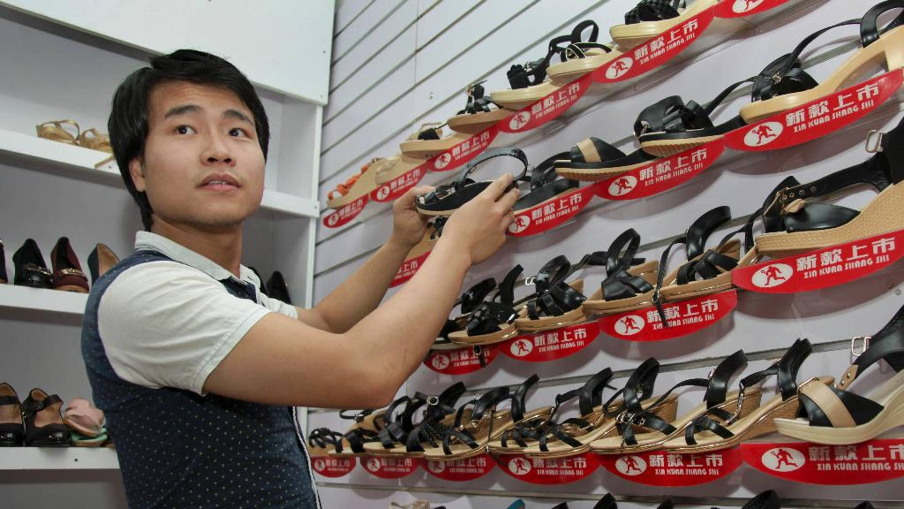 FILE--In this a Tuesday, June 23, 2015 file photo,  ofChinese national Wei Kun  as he adjusts a display as he waits for customers at his shoe shop in Kampala, Uganda. Years of growing animosity at Chinese traders turned into a protest by hundreds in Uganda's capital on Wednesday April 19, 2017  against what local businesses called unfair competition, while the mayor warned against the tensions turning into xenophobic attacks. (AP Photo/Stephen Wandera-File)