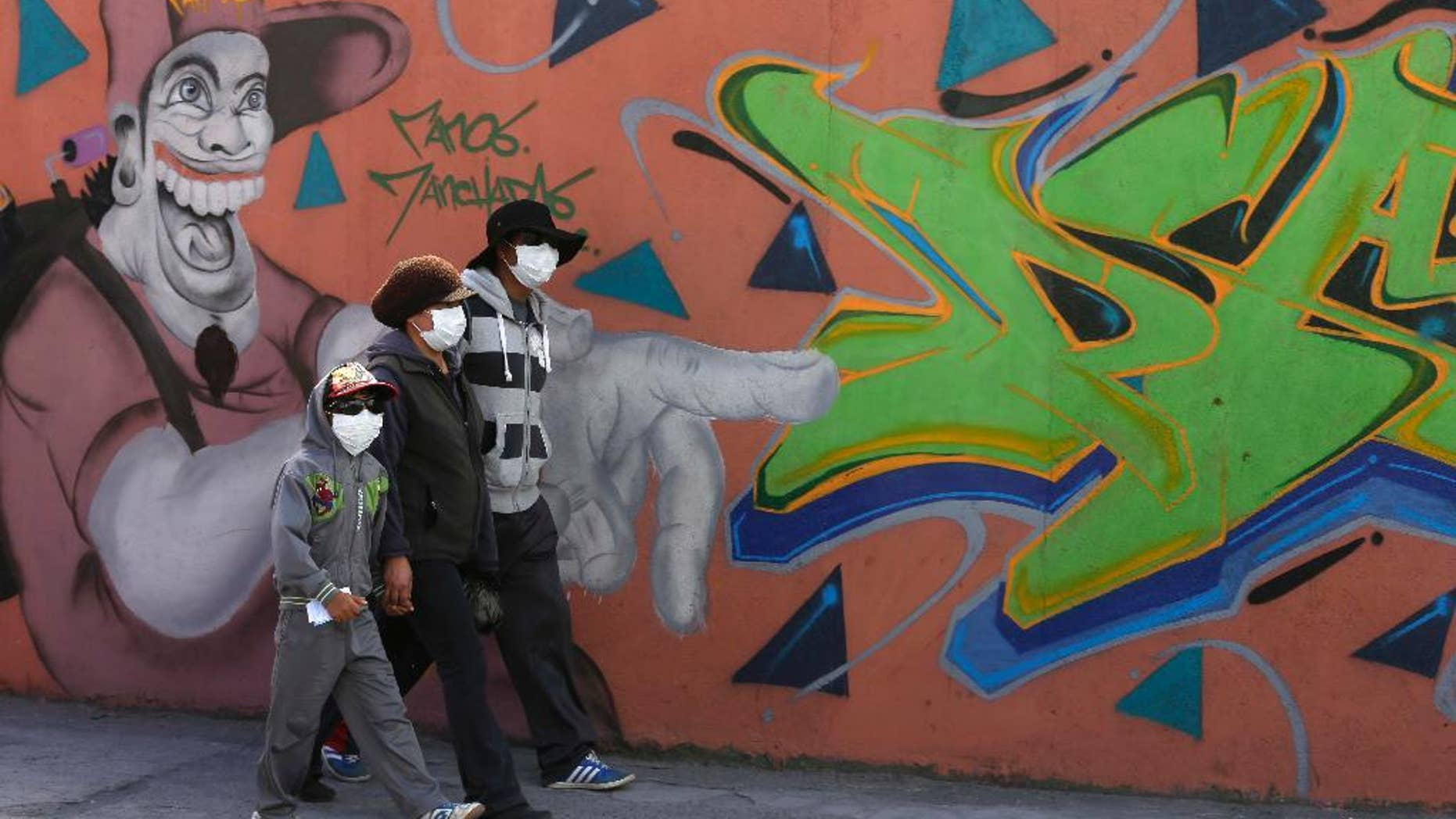 Residents wear masks to protect themselves from volcanic ash spewed from the Cotopaxi volcano, in Machachi, Ecuador, Friday, Aug. 14, 2015. The Cotopaxi volcano near Ecuador's capital has spewed ash over a wide area in two pre-dawn blasts. The volcano is considered one of the world's most dangerous volcanoes due to a glacial cover that makes it prone to mud flows and its proximity to a heavily populated area, but government scientists say that the snow-capped volcano doesn't seem to be on the verge of a major eruption. Its last major eruption was in 1877. (AP Photo/Dolores Ochoa)
