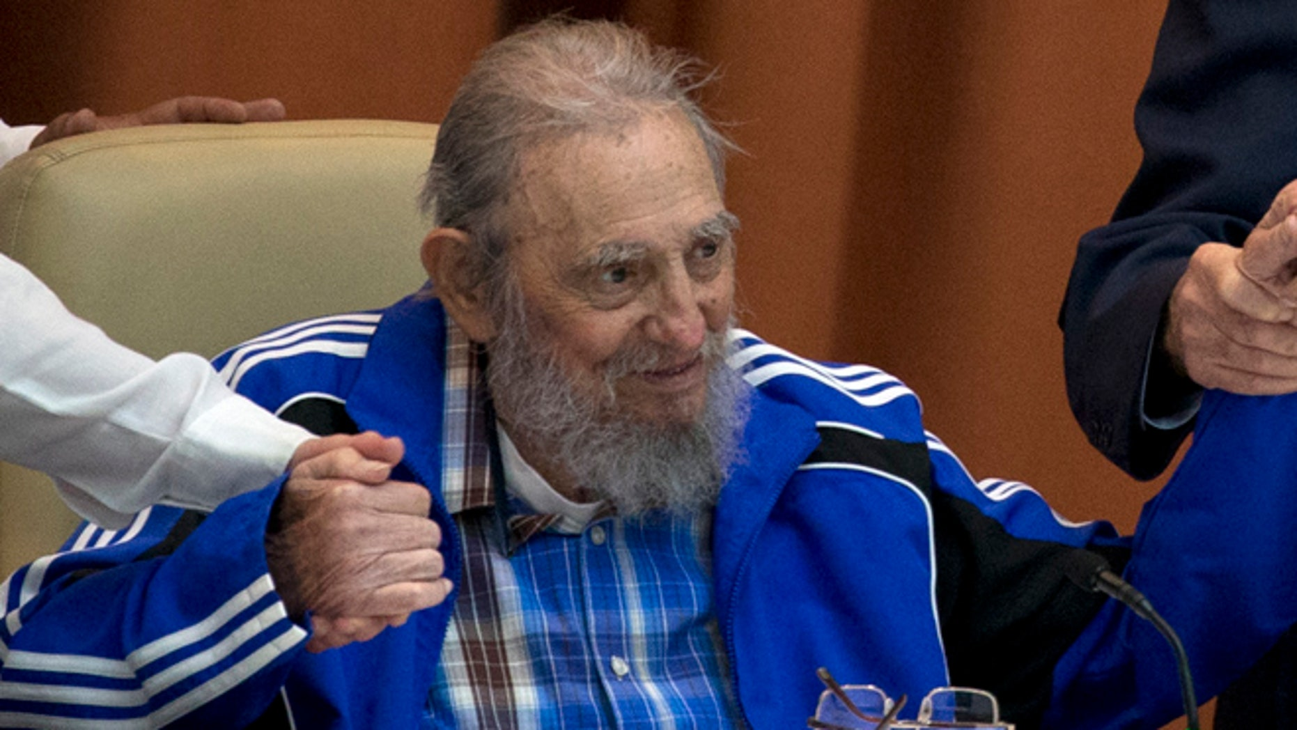 April 19: Fidel Castro sits as he clasps hands with his brother, Cuban President Raul Castro, right, and second secretary of the Central Committee, Jose Ramon Machado in Havana.