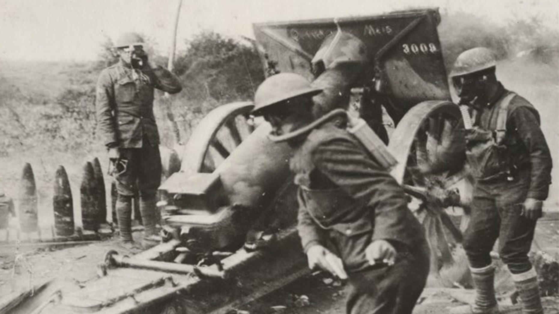 American soldiers in the Army's 108th Field Artillery – under fire from enemy gas shells – strike back in Varennes-en-Argonne, France.