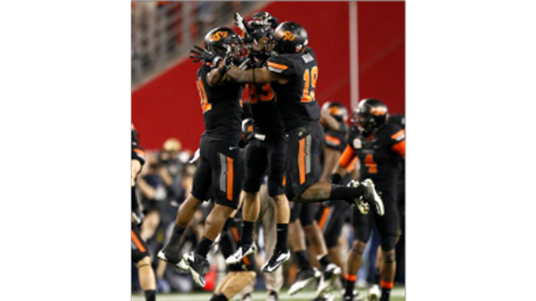 Oklahoma State cornerback Brodrick Brown (19), Colton Chelf, center, and Shaun Lewis, right, celebrate a missed field goal attempt by Stanford during overtime of the Fiesta Bowl NCAA college football game Monday, Jan. 2, 2012, in Glendale, Ariz.
