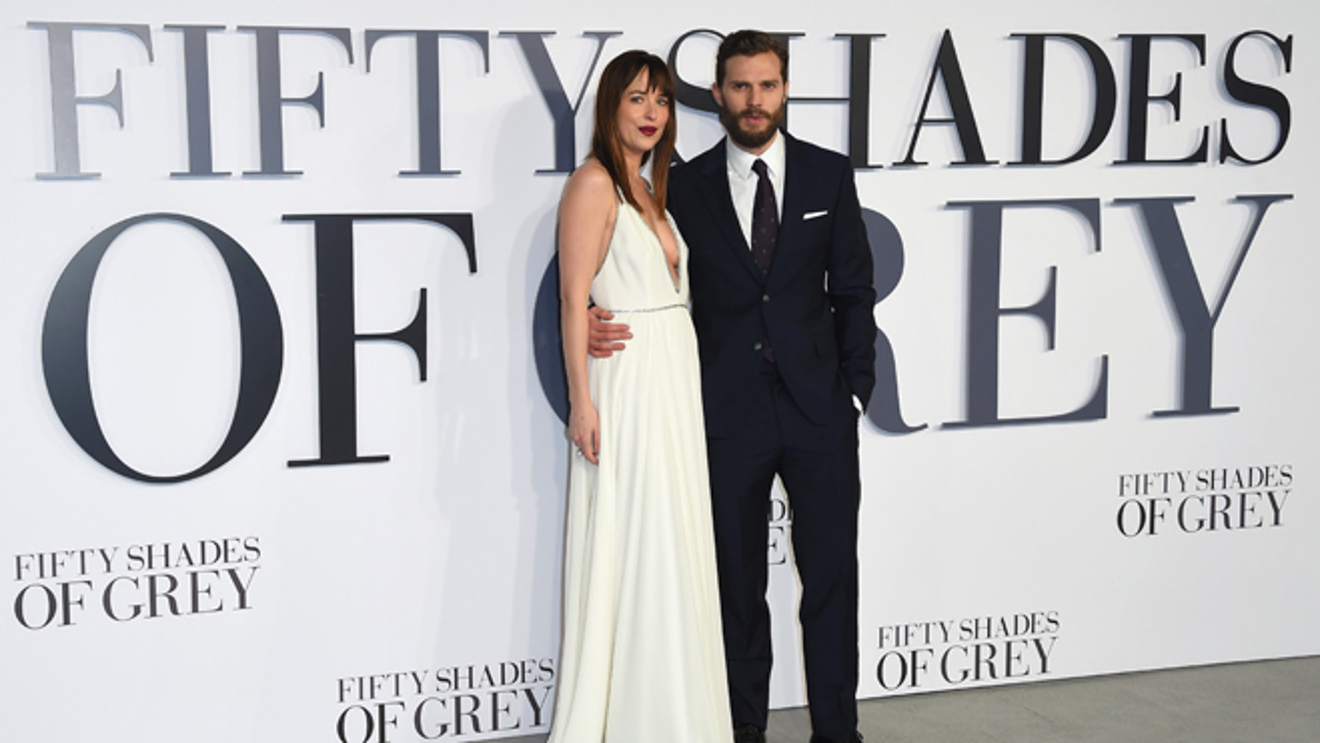 """Feb. 12, 2015. Dakota Johnson and Jamie Dornan pose for photographers at the UK Premiere of """"Fifty Shades of Grey."""""""