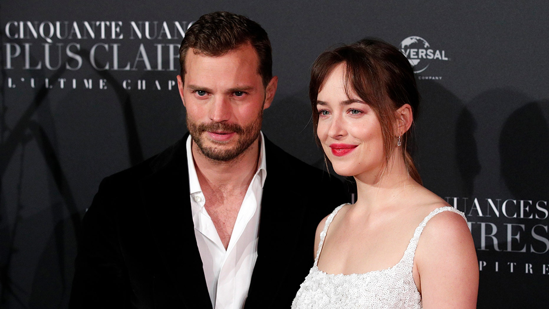 Jamie Dornan, left, and Dakota Johnson pose during a photocall for the world premiere of 'Fifty Shades Freed - 50 Nuances Plus Claires' at Salle Pleyel in Paris, Tuesday, Feb. 6, 2018. (AP Photo/Francois Mori)