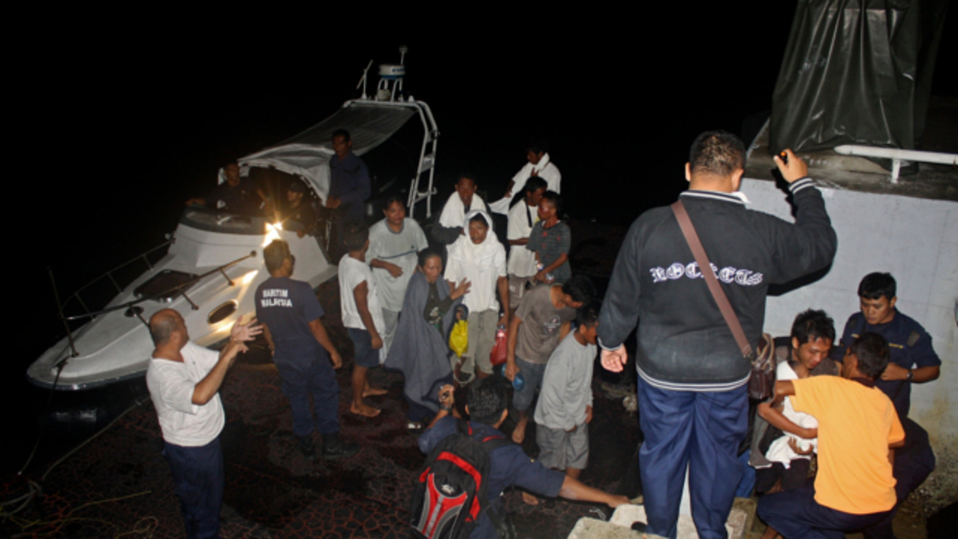 FILE: July 18, 2013: This photo released by Malaysian Maritime Enforcement Agency shows Indonesian passengers who were rescued from an overturned boat at a jetty in Tanjung Sedili, Johor state, Malaysia.