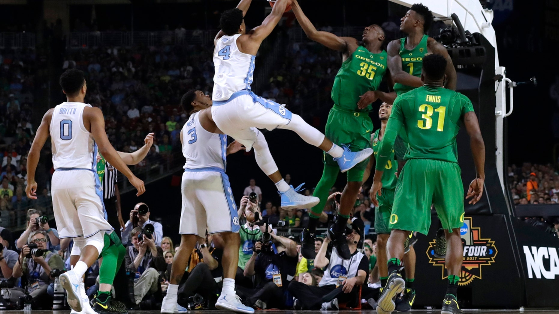North Carolina forward Isaiah Hicks (4) dunks the ball over Oregon's Kavell Bigby-Williams (35) and Jordan Bell (1) during the first half in the semifinals of the Final Four NCAA college basketball tournament, Saturday, April 1, 2017, in Glendale, Ariz. (AP Photo/David J. Phillip)