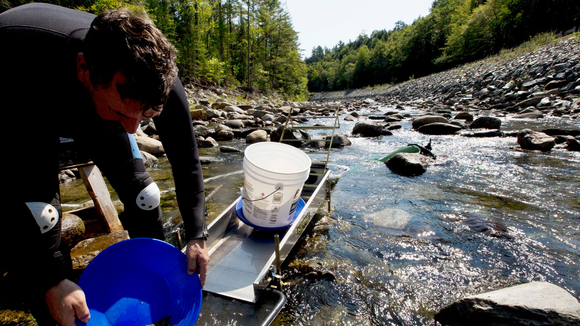 In this photo taken Sunday, Sept. 4, 2016, Chris Hall uses a sluice box to pan for gold in the Wild Ammonoosuc River in Bath, N.H.