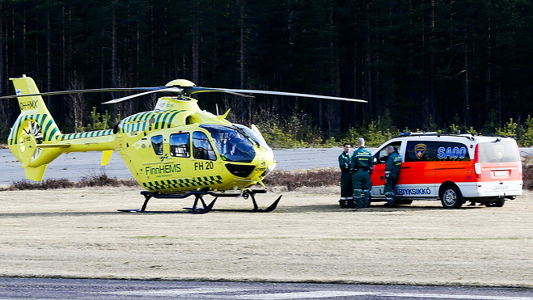 April 20, 2014: A helicopter and an ambulance are seen at the Jamijarvi Airfield, southwest Finland. A small passenger plane carrying parachuters fell to the ground near the airfield on Sunday afternoon. The police say that there are more than three victims. Three people out of 11 on the plane were rescued.