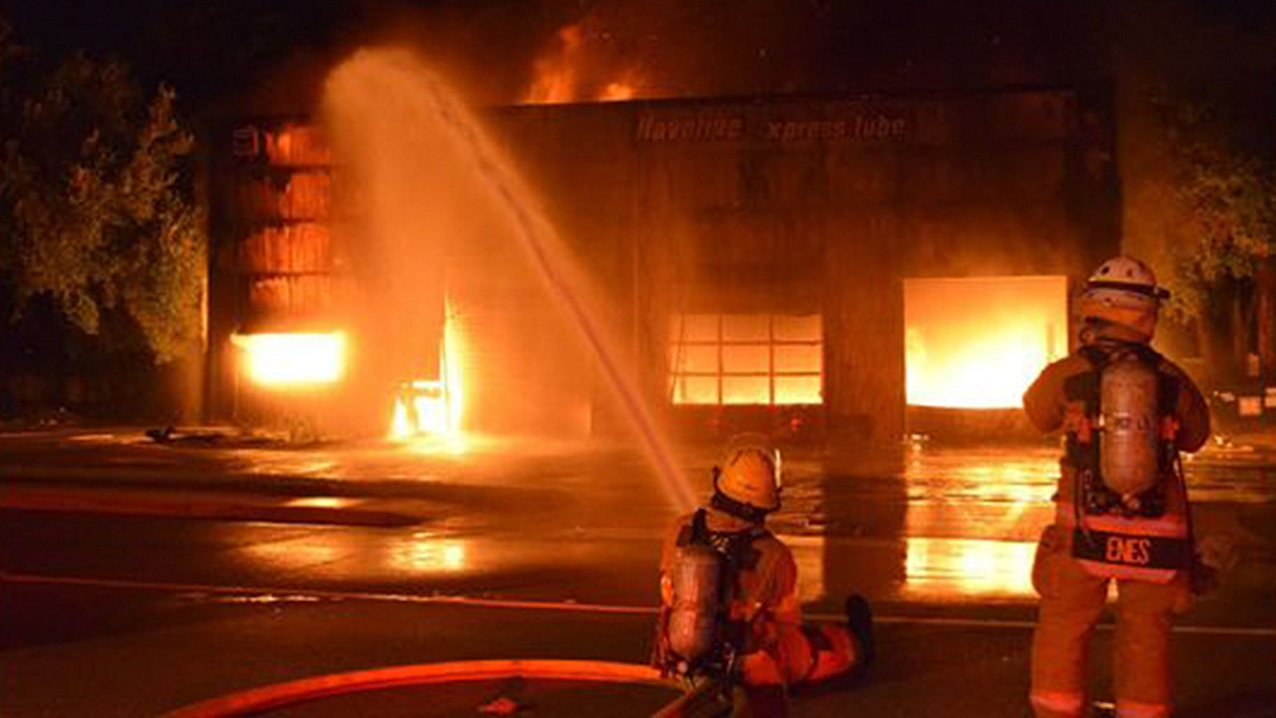 Firefighters shoot water at an intense structure fire ignited by a hit-and-run crash at a Havoline Express Lube.