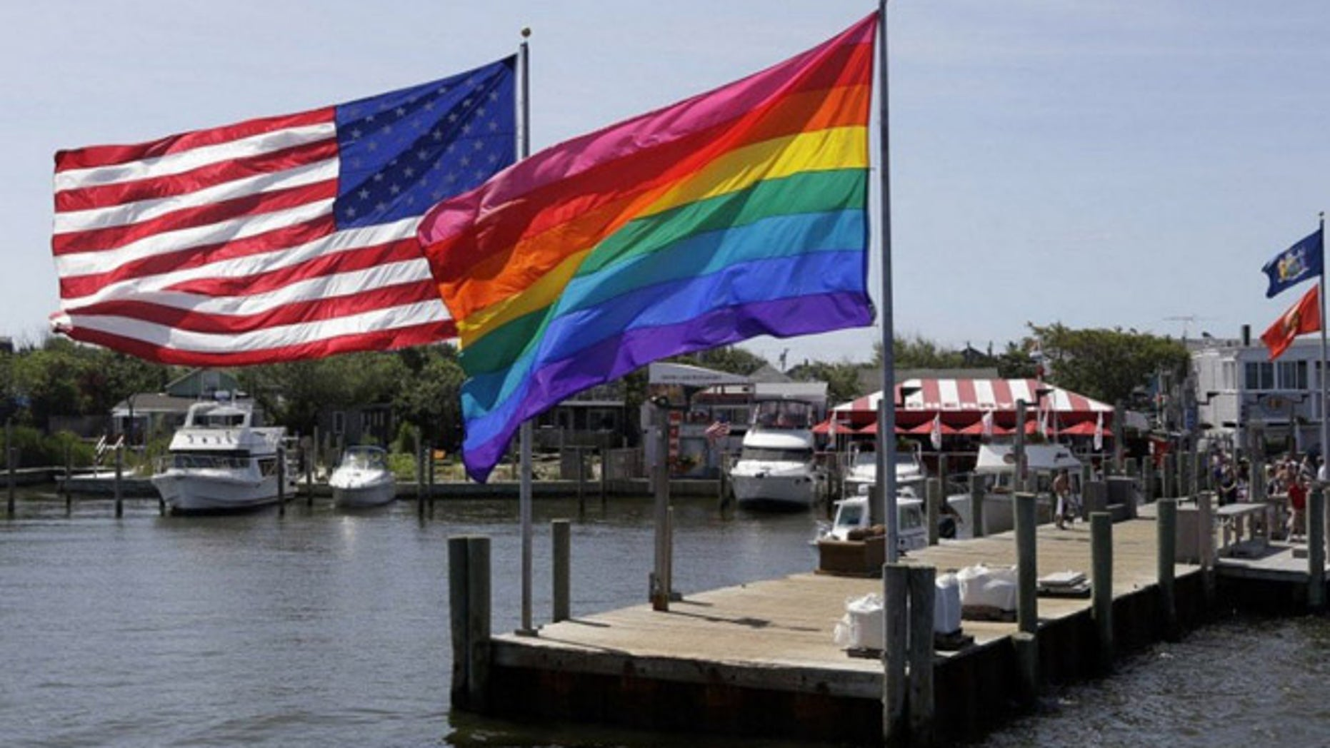An American flag and a gay pride banner wave together on Fire Island, a barrier island off New York that is a popular summer destination for LGBT revelers. (AP)