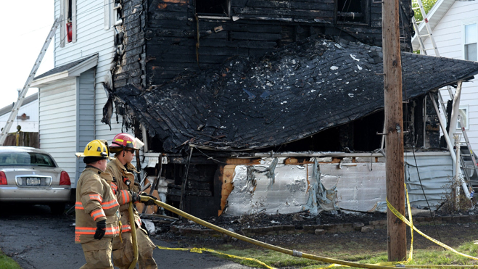 Syracuse firefighters begin to clean up at the scene of a fatal fire, Friday May 6, 2016, in Syracuse, N.Y. The blaze was reported early Friday morning. (Michael Greenlar/The Syracuse Newspapers via AP) NO SALES; MANDATORY CREDIT