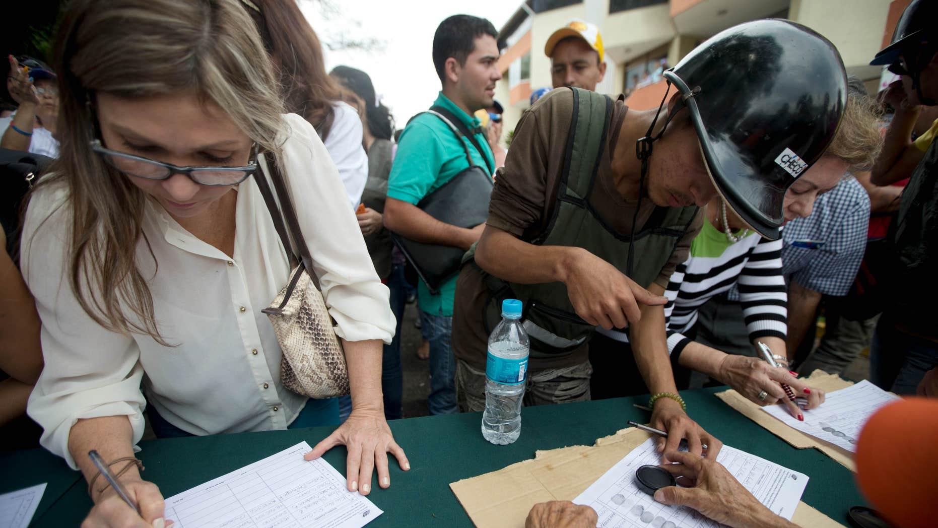 Venezolanos firman una petición que promueve la oposición, para iniciar un referendo revocatorio del mandato del presidente de Venezuela Nicolás Maduro en San Cristóbal, el miércoles 27 de abril de 2016. (Foto AP/Fernando Llano)