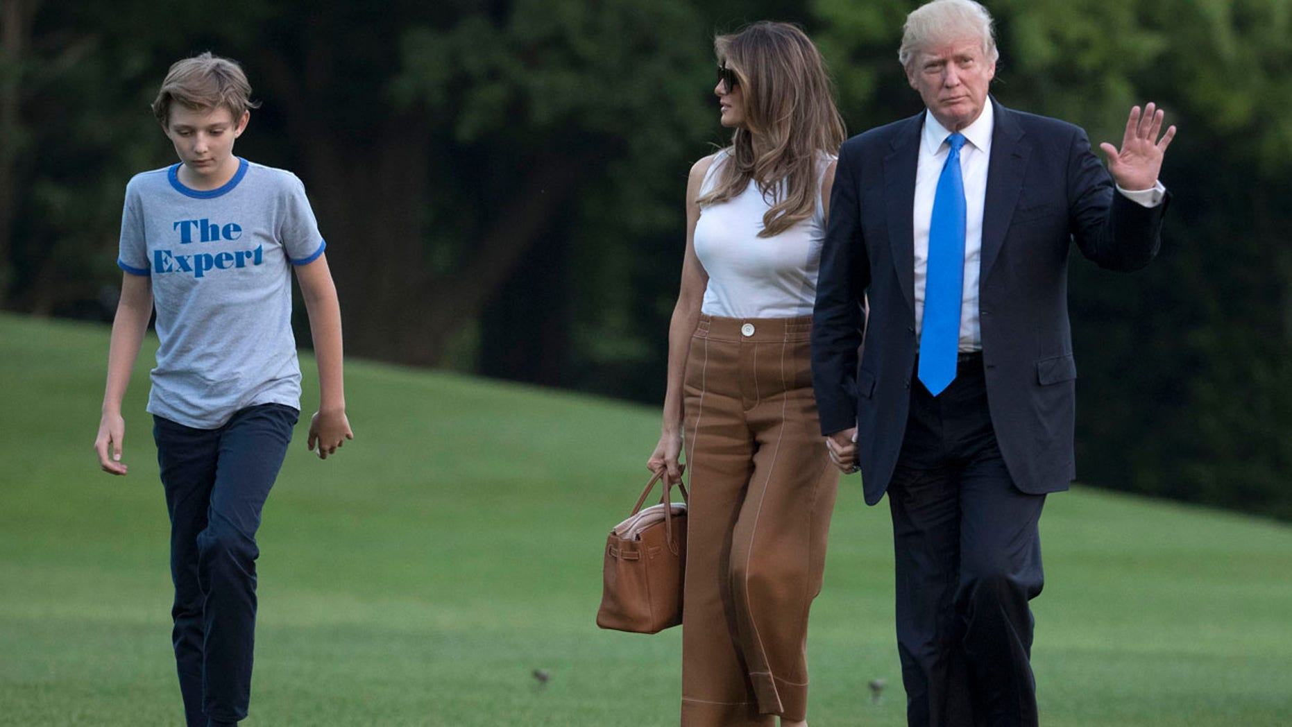 President Donald Trump waves as he walks with first lady Melania Trump and their son, Barron Trump, from Marine One across the South Lawn to the White House in Washington, Sunday, June 11, 2017, as they returned from Bedminster, N.J. (AP Photo/Carolyn Kaster)