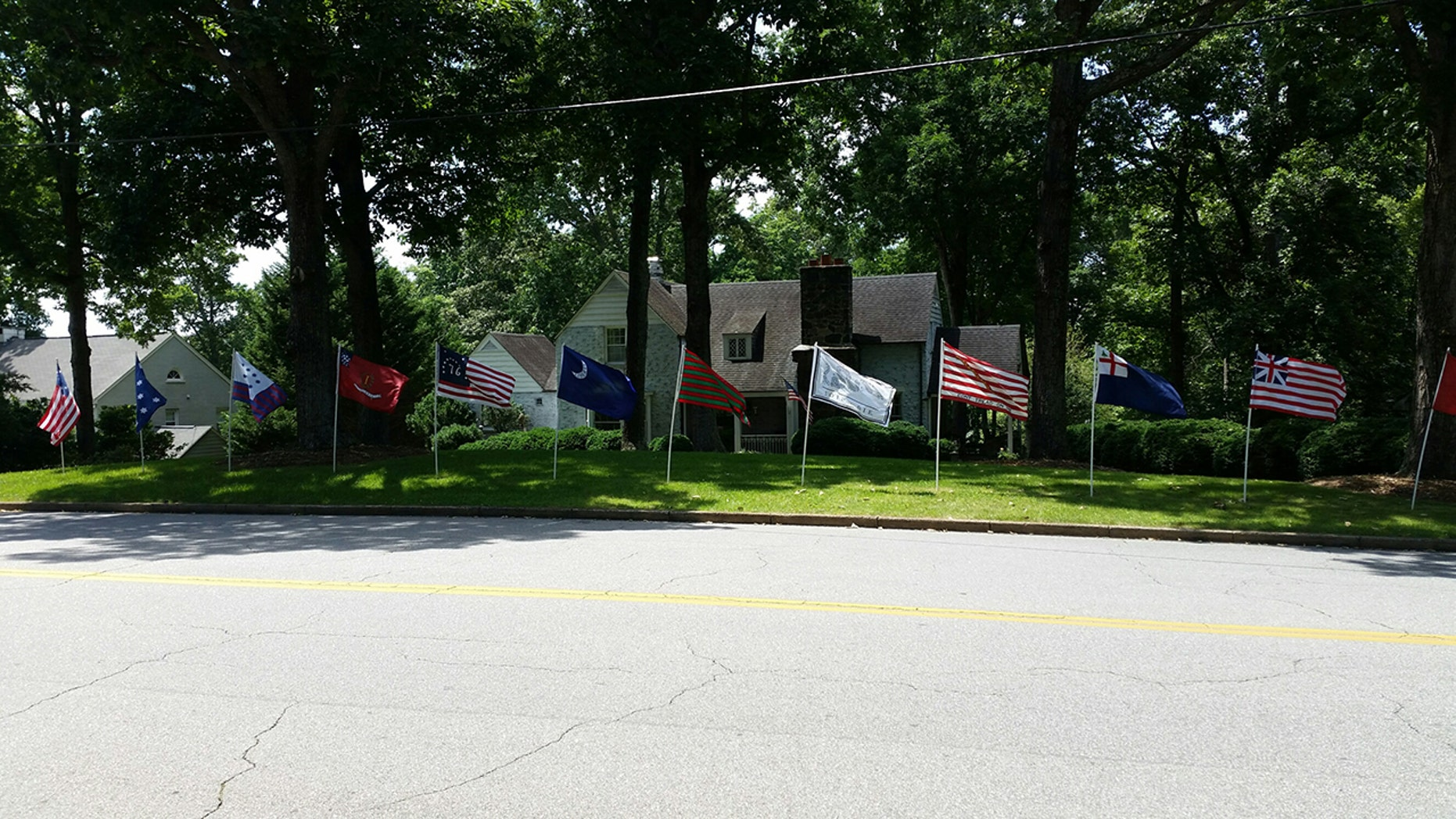 Revolutionary War-era flags stand in Eric Monday's front yard in Martinsville, Va.