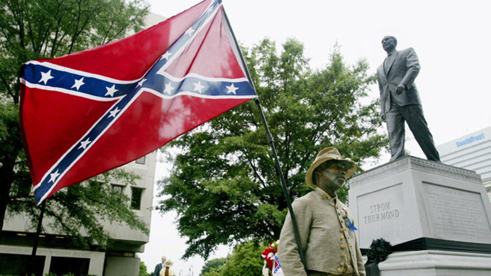 July 1, 2003: Wearing a Confederate uniform and the Stars and Bars of theConfederacy, H.K. Edgerton of Ashville, North Carolina stands beside astatue of former Sen. Strom Thurmond outside the state house in Columbia, South Carolina. (Reuters)